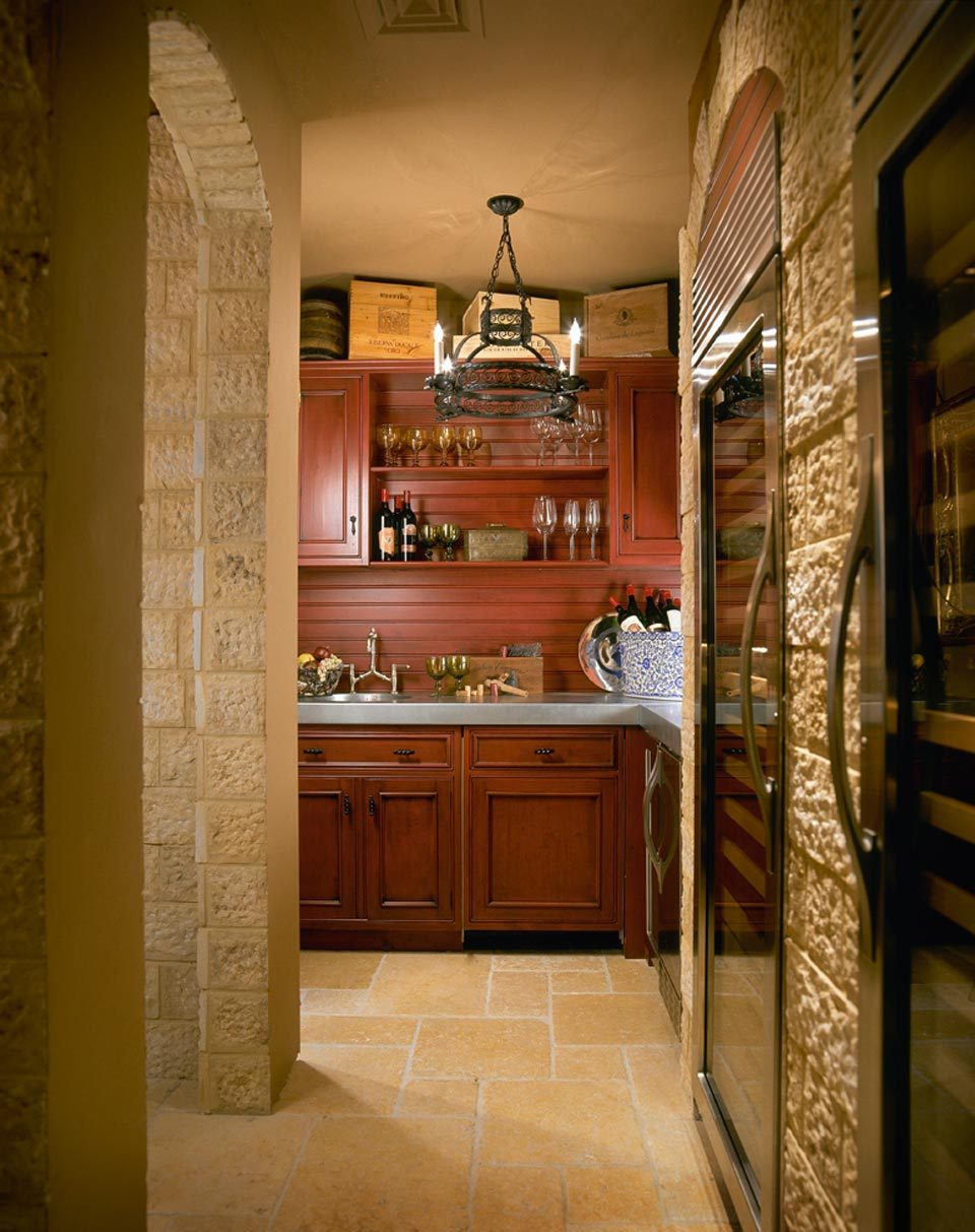 Wet bar area of wine cellar features cherry-stained, shaker style cabinetry by Bilotta, grey quartz countertop and a round stainless drop-in sink. Exposed stone walls lead into the storage area of the wine cellar. The room is accented by a round wrought iron chandelier and rustic gold slate flooring. Design by Regina Bilotta of Bilotta Kitchens.