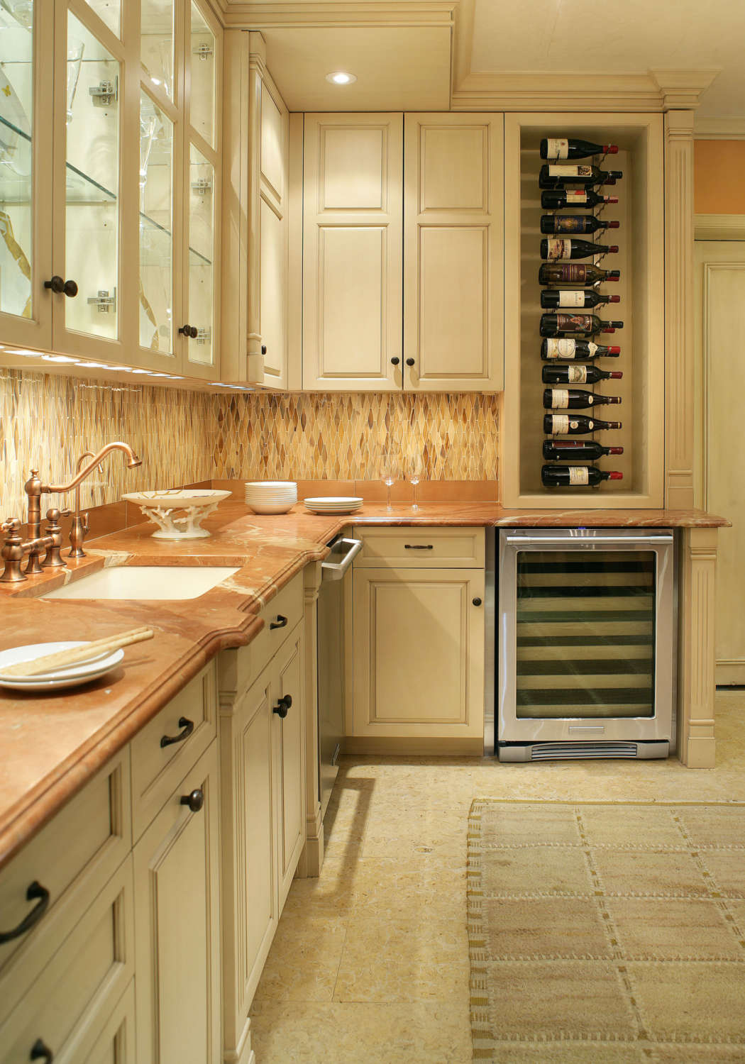 Butler's pantry features linen white painted fully custom, frameless Rutt handcrafted cabinets with glass fronts and oil-rubbed bronze hardware, vertical wine rack, toffee-colored marble countertops, bronze faucet and neutral warm-toned backsplash and floor tiles. Design by Regina Bilotta of Bilotta Kitchens.