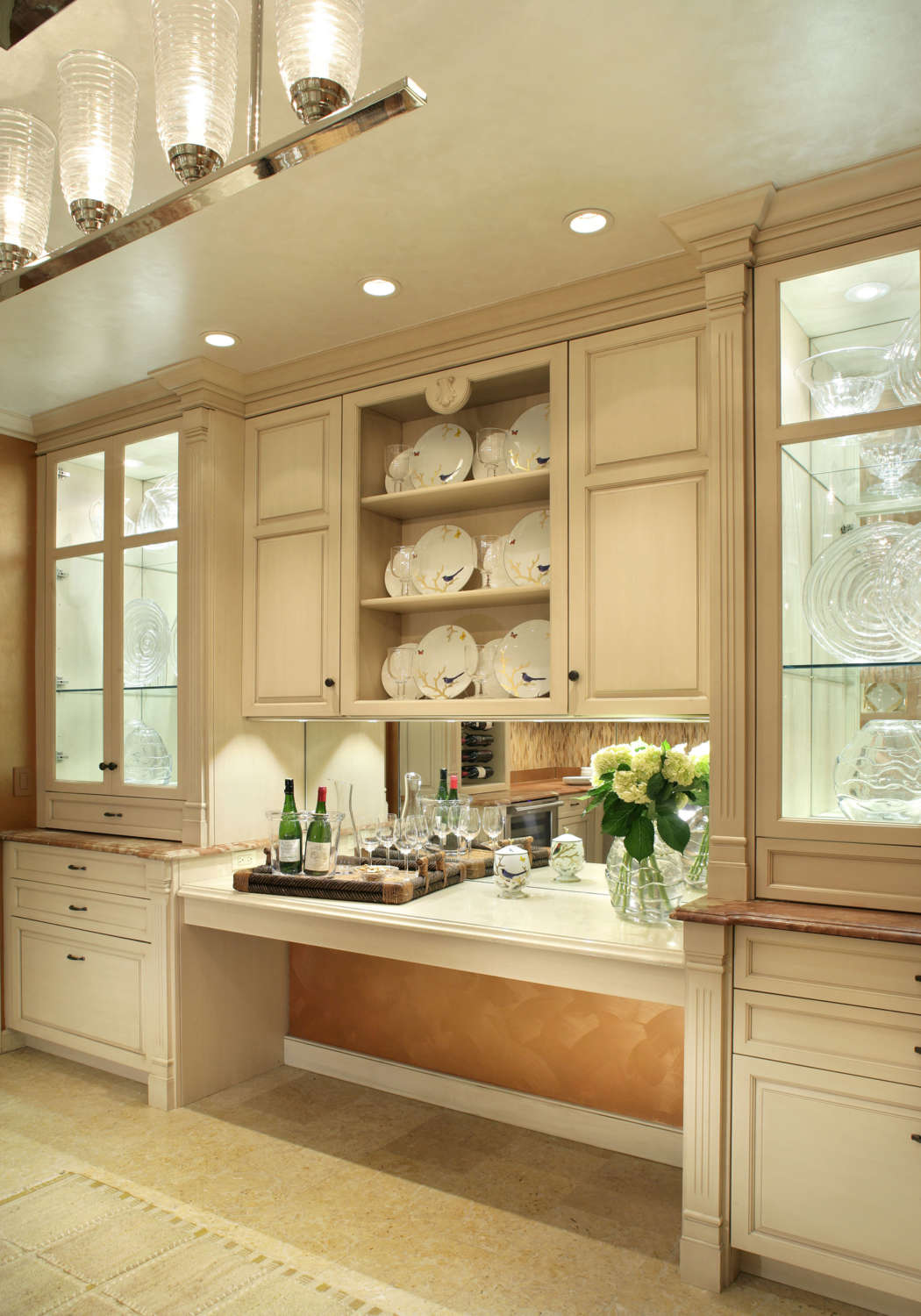 Light-filled butler's pantry features linen white painted fully custom, frameless Rutt Handcrafted Cabinetry, mirror backsplash for bar area and toffee-colored marble countertops. Open shelving and interior lit, custom china cabinets with glass fronts provide ample storage. Design by Regina Bilotta of Bilotta Kitchens.