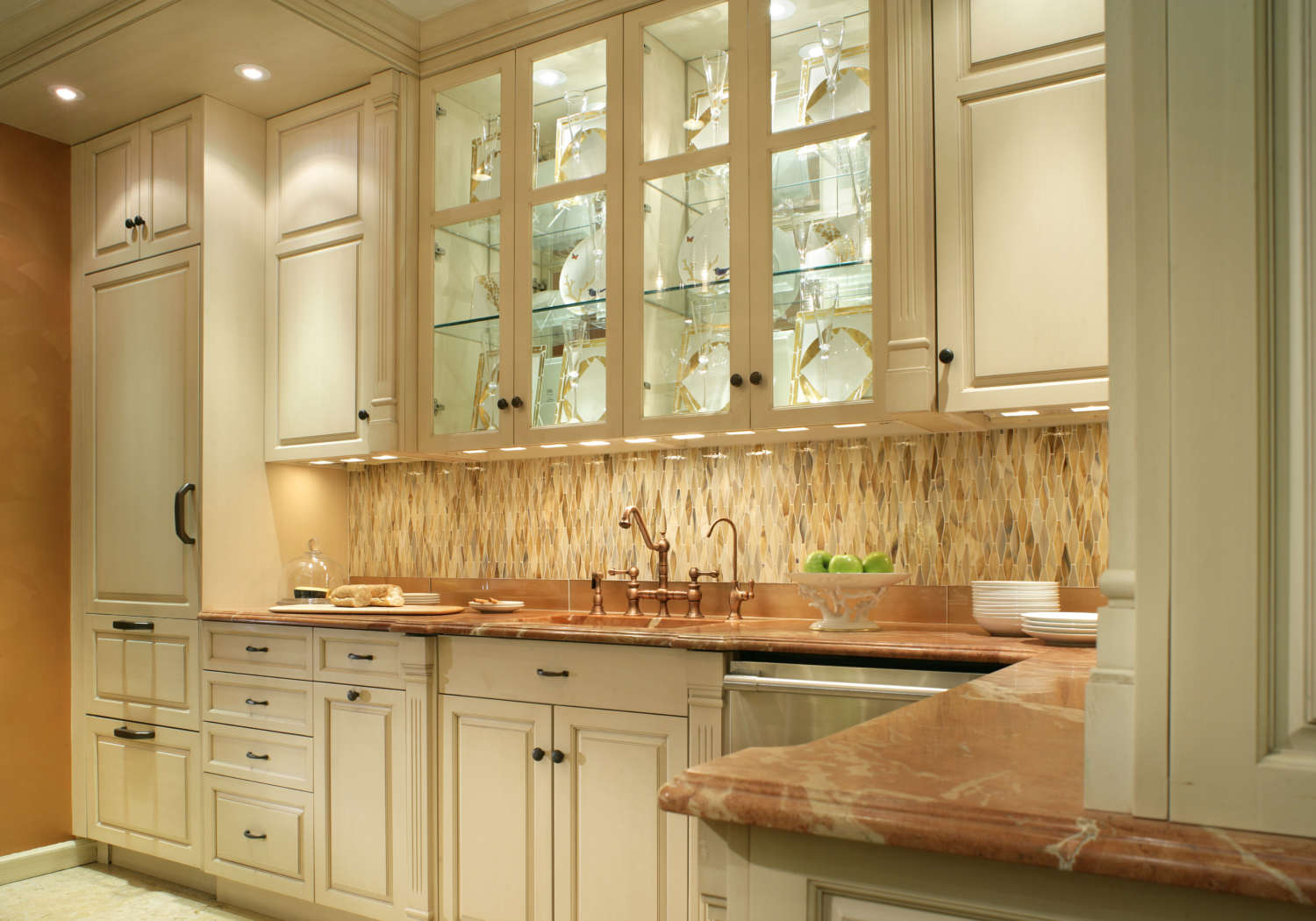 Light-filled butler's pantry features linen white painted fully custom, frameless Rutt Handcrafted Cabinetry with oil-rubbed bronze hardware, toffee-colored marble countertops and a warm-toned geometric backsplash. The interior lit custom china cabinets have glass fronts and reflect off the bronze sink hardware. Design by Regina Bilotta of Bilotta Kitchens.