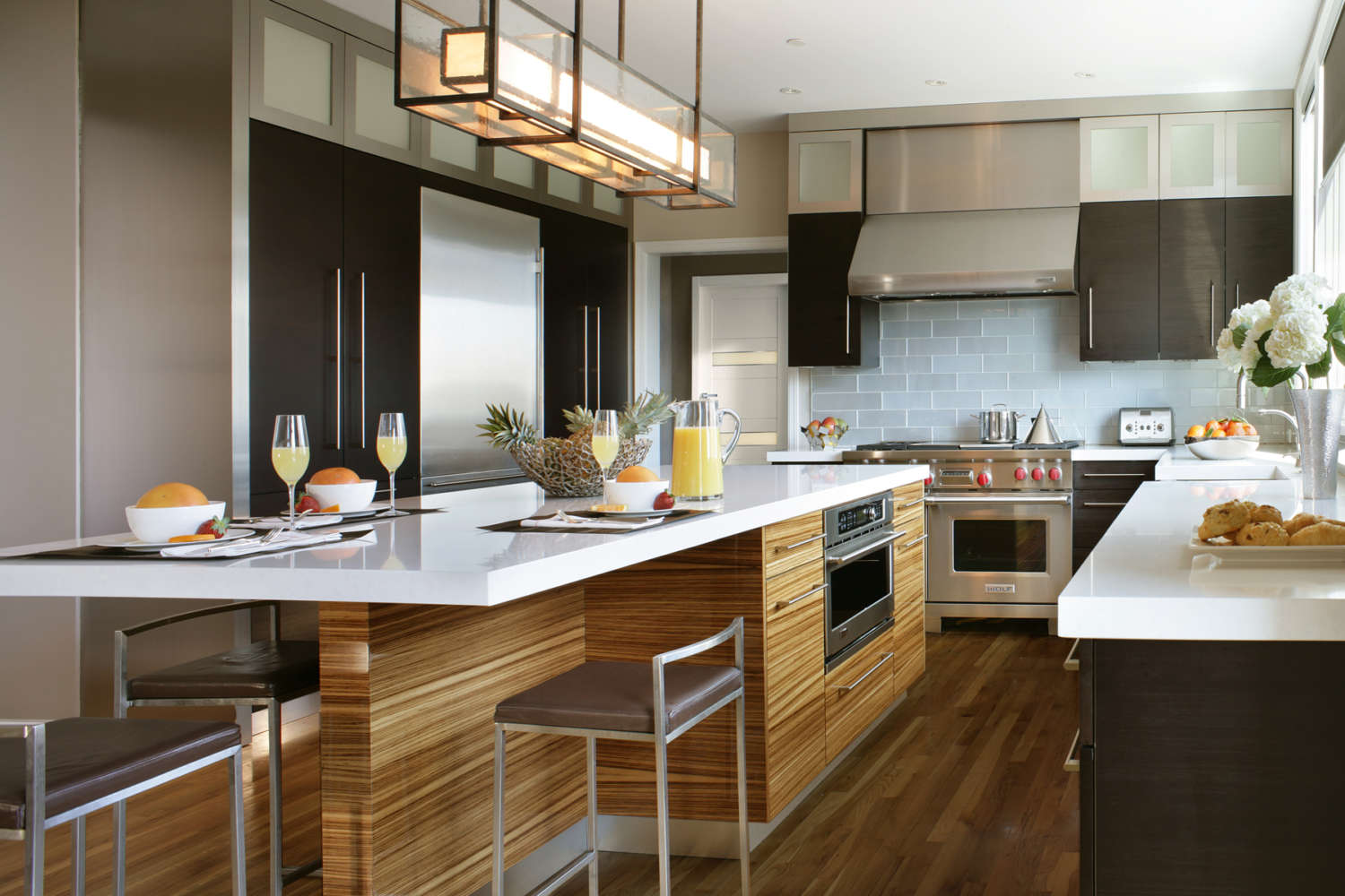 Modern kitchen with black pine laminate flat panel, frameless Artcraft cabinets and zebrawood laminate island with seating. Brushed stainless elements and glass subway tiles provide textural accents. Design by Peter Bittner of Bilotta Kitchens.