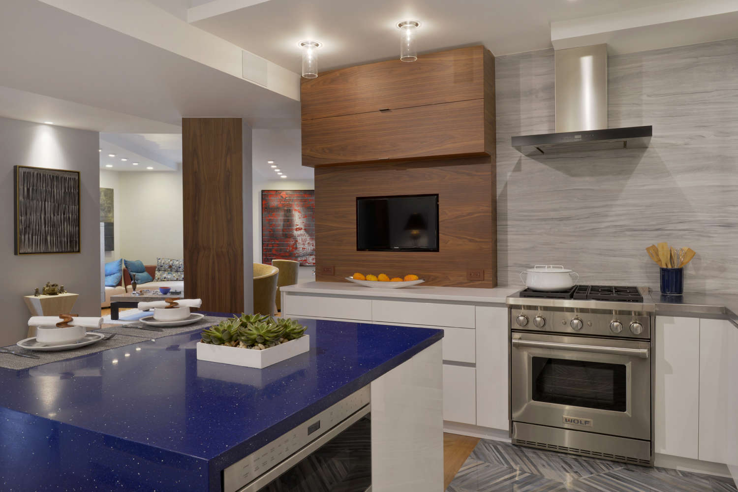 Contemporary kitchen with fully custom natural walnut and white high-gloss flat panel, frameless Artcraft cabinetry opens up into an adjacent seating area. Small island has cobalt blue top, and counters are edged with brushed aluminum. Design by Tom Vecchio of Bilotta Kitchens.