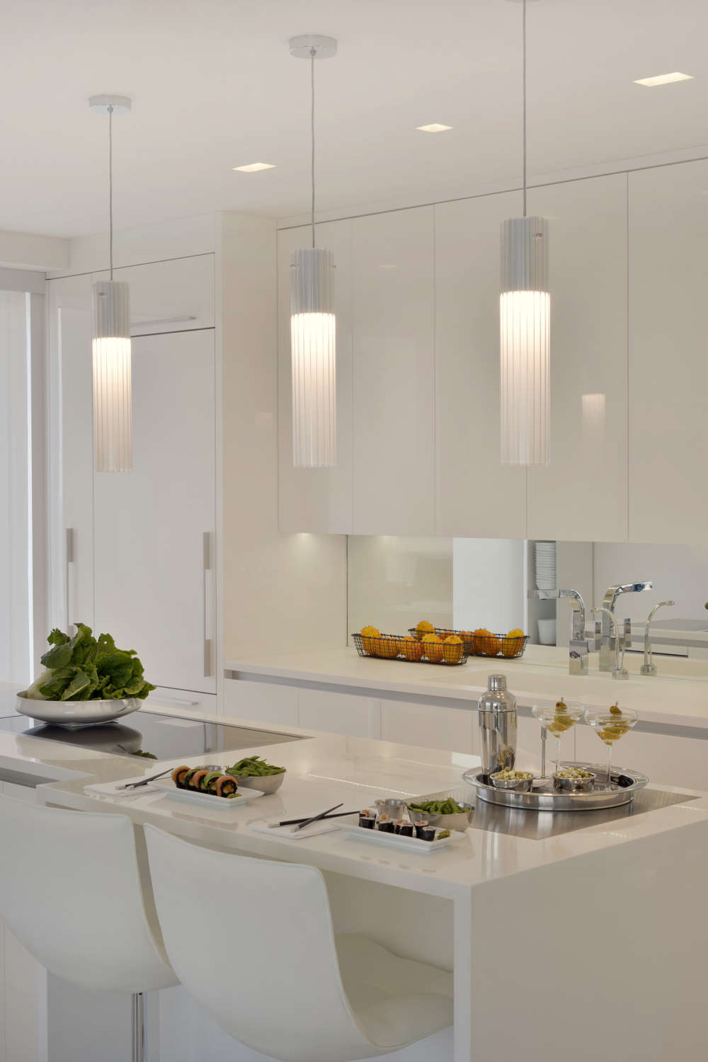 All white contemporary kitchen features high gloss white fully custom flat panel, frameless Artcraft Cabinetry with channel hardware and white quartz countertops. Island with seatign is accented by dramatic white pendant ligting. Design by Goran Savic of Bilotta Kitchens.