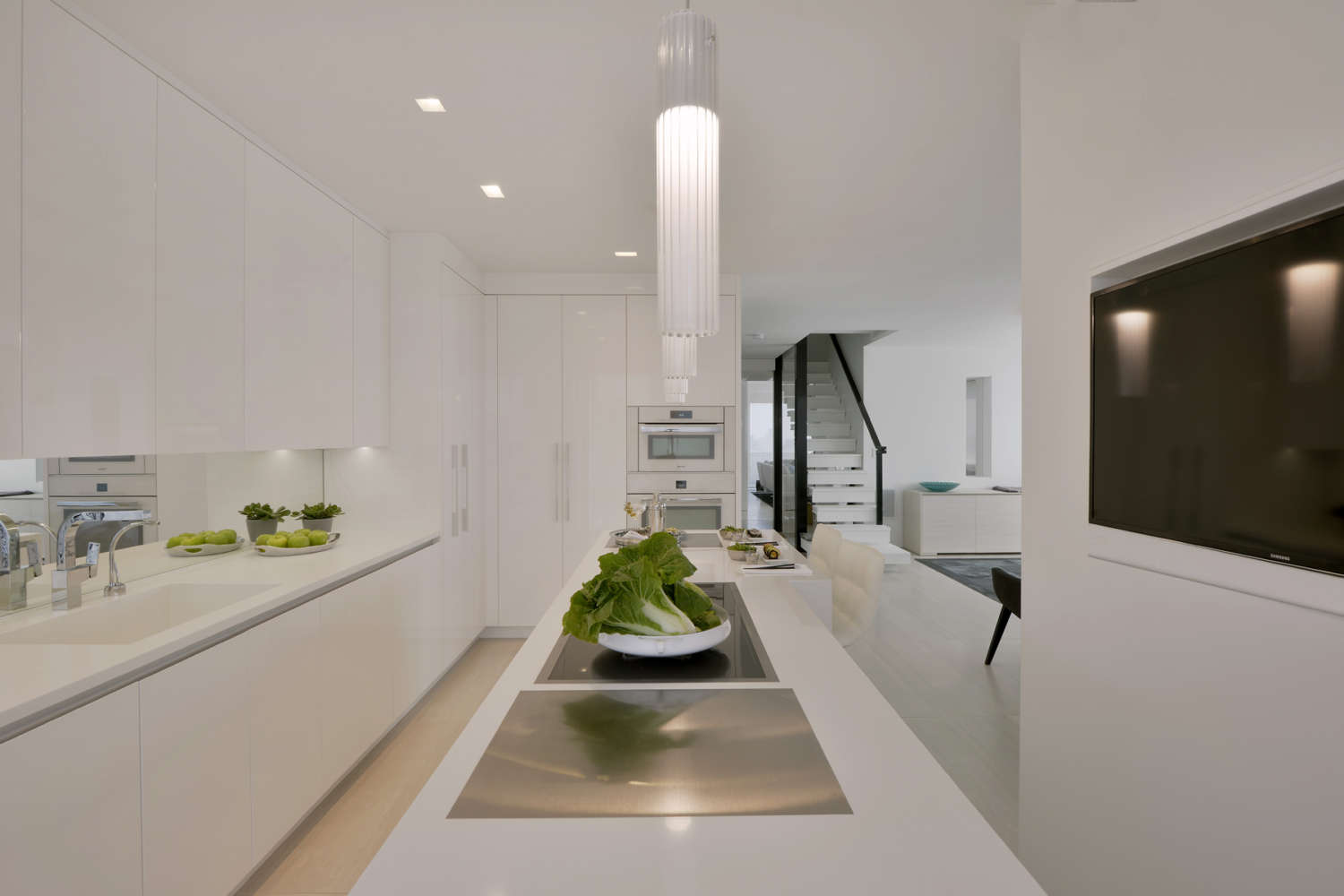 L-shaped all white contemporary kitchen features flat panel, frameless fully custom Artcraft Cabinetry in high gloss white with channel hardware and white quartz countertops. Design by Goran Savic of Bilotta Kitchens.