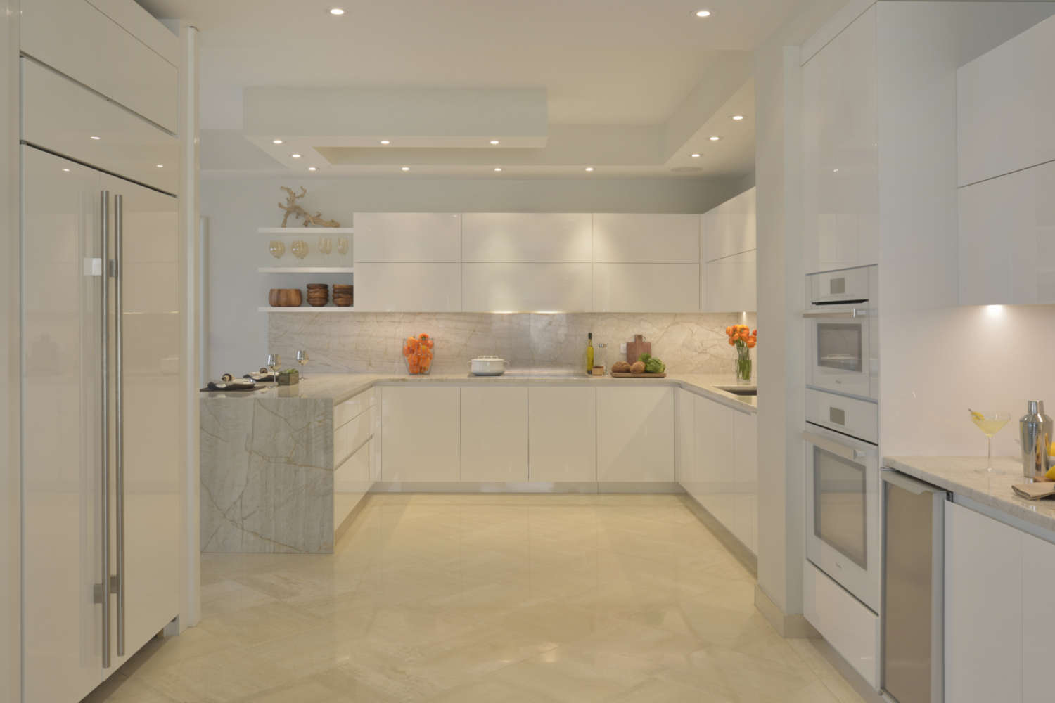 U-shaped kitchen is designed with soft lighting and a palette of warm whites. The fully custom cabinets are ArtCraft flat panel, frameless in high gloss white, countertops and backsplash are light marble with veining, and the floor is a light porcelain tile. Open shelving is used for display. Design by Tabitha Tepe of Bilotta Kitchens.