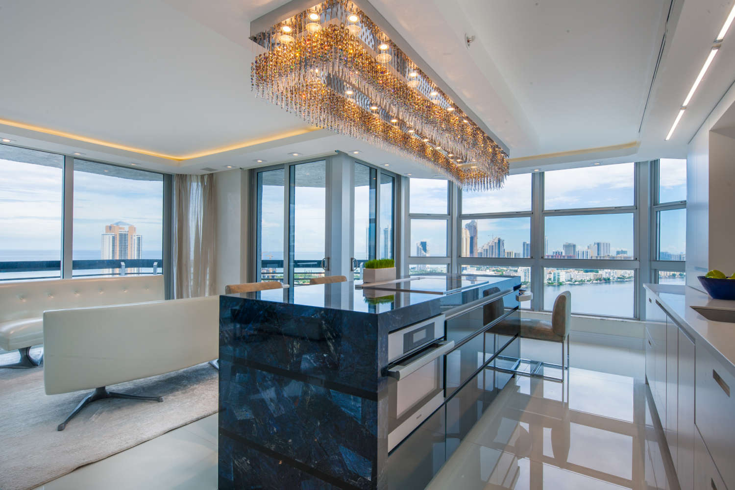 Florida penthouse kitchen features flat panel, frameless fully custom Artcraft cabinetry in a mix of semi gloss white and Galaxy glass, an island with seating. Kitchen opens up into the living room area. Design by Peter Bittner of Bilotta Kitchens.