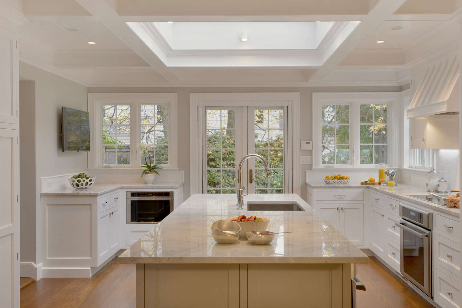 U-shaped kitchen with eat-at island and wood range hood. Features fully custom white painted Rutt Regency cabinets. Designed by Fabrice Garson of Bilotta Kitchens.