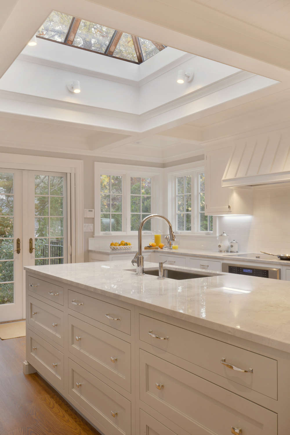 Traditional kitchen with skylight, white painted fully custom Rutt Regency cabinets, light countertops and natural oak flooring. Designed by Fabrice Garson of Bilotta Kitchens.