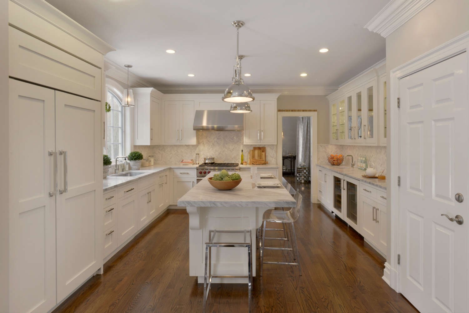 U-shaped kitchen with fully custom Bilotta cabinets. Kitchen features a large island with seating, wood paneled appliances, light gray counters, stainless accents and a mix of white painted cabinets and glass front cabinet doors. Designed by Linda Daniele of Bilotta Kitchens.