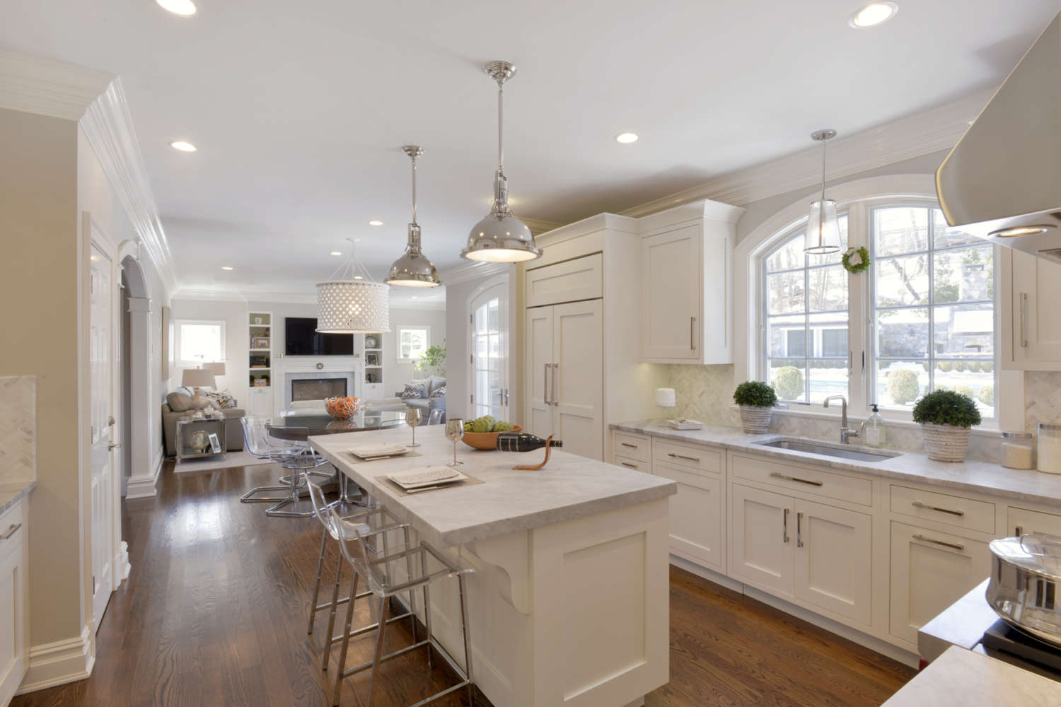 Bright kitchen with fully custom white painted Bilotta cabinets, light gray countertops and natural oak flooring opens into the living room. White painted kitchen island has seating and extra thick top. Designed by Linda Daniele of Bilotta Kitchens.