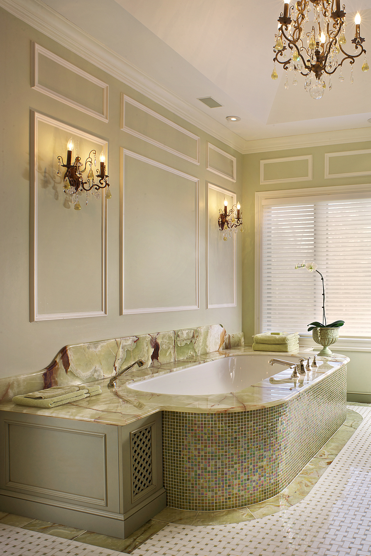 Large master bath features pistachio green painted walls with white molding accents, gold tone chandelier and wall sconces. The custom wood tub surround by Bilotta Cabinetry has light green marble with brown veining, as well as small pistachio green, gold and brown tiles. Design by Regina Bilotta of Bilotta Kitchens.