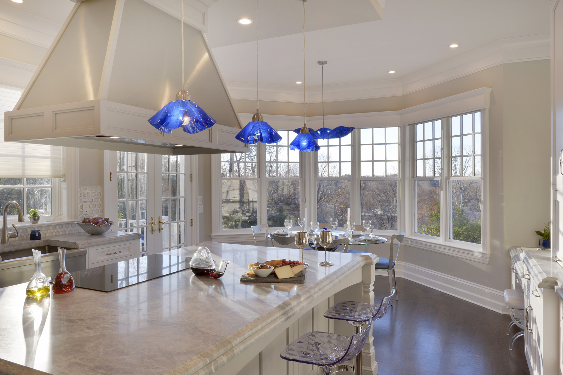 Bright U-shaped kitchen with white painted fully custom Bilotta cabinets, light marble countertops, island hood in wood and stainless steel, and blue glass pendant lights. Designed by Fabrice Garson of Bilotta Kitchens.