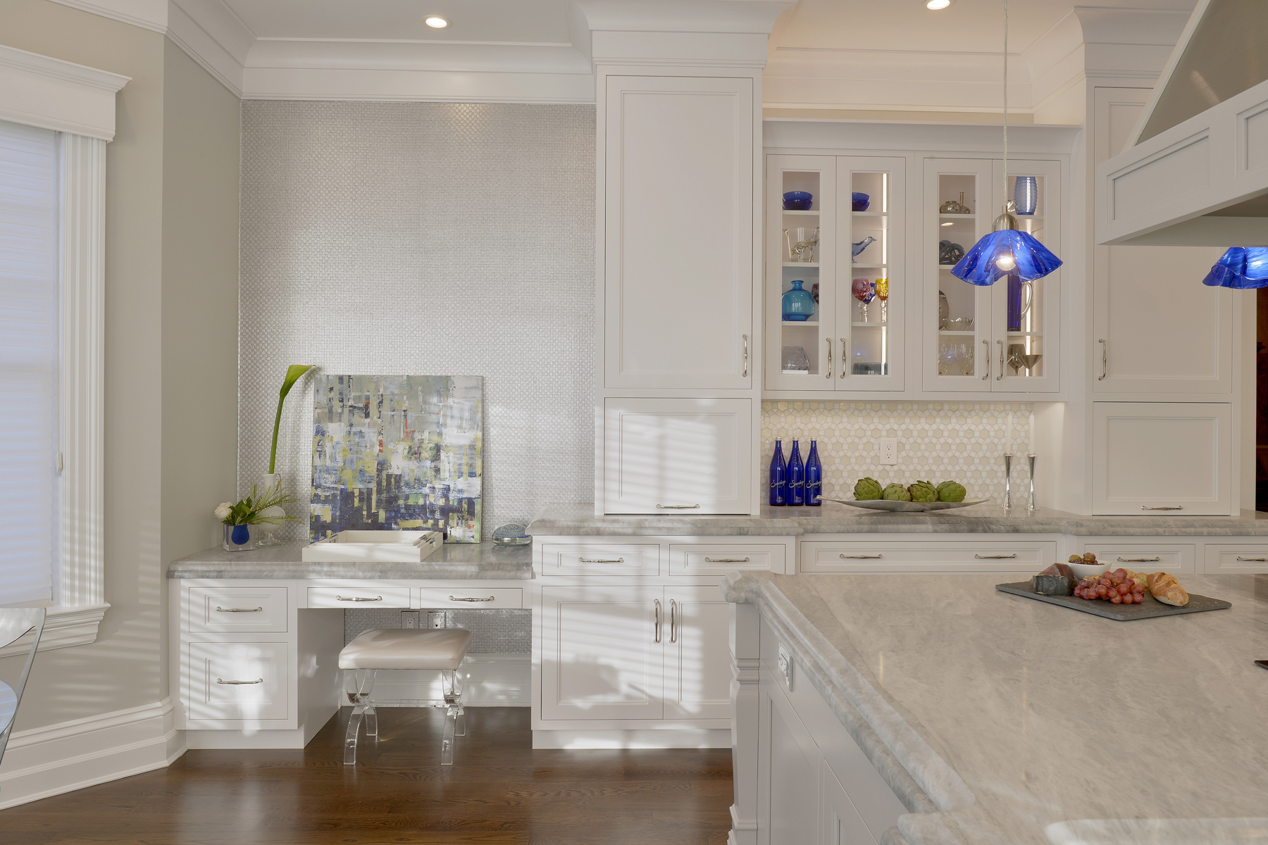 Bright U-shaped kitchen with white painted fully custom Bilotta cabinets, light marble countertops, and desk in kitchen. Cabinet fronts are a mix of full panel and glass front doors. Designed by Fabrice Garson of Bilotta Kitchens.