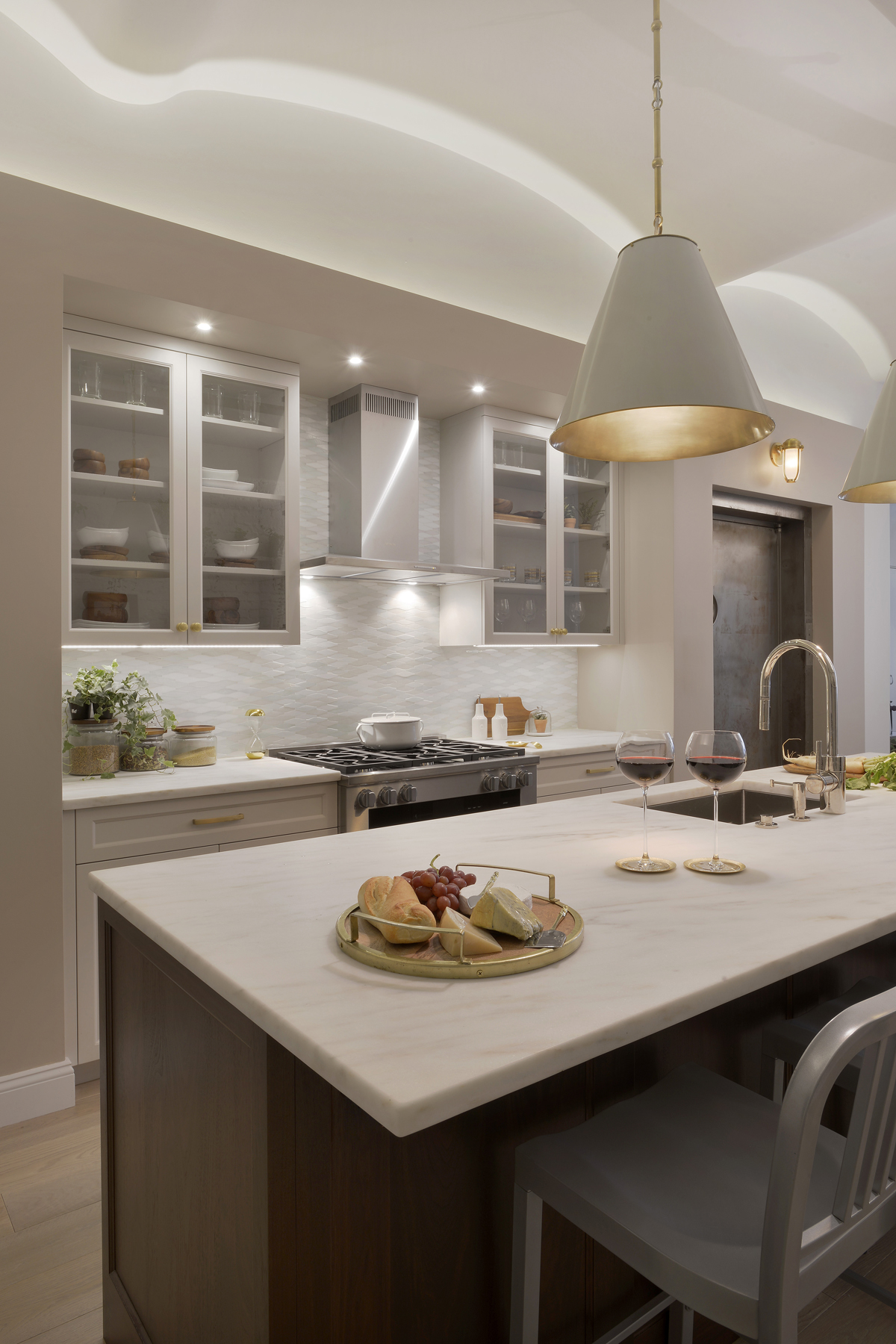 NYC loft kitchen features high celings, marble-topped walnut island with seating, and white painted, frameless shaker style cabinets by Bilotta. Upper cabinets have glass fronts. Design by Tabitha Tepe of Bilotta Kitchens.
