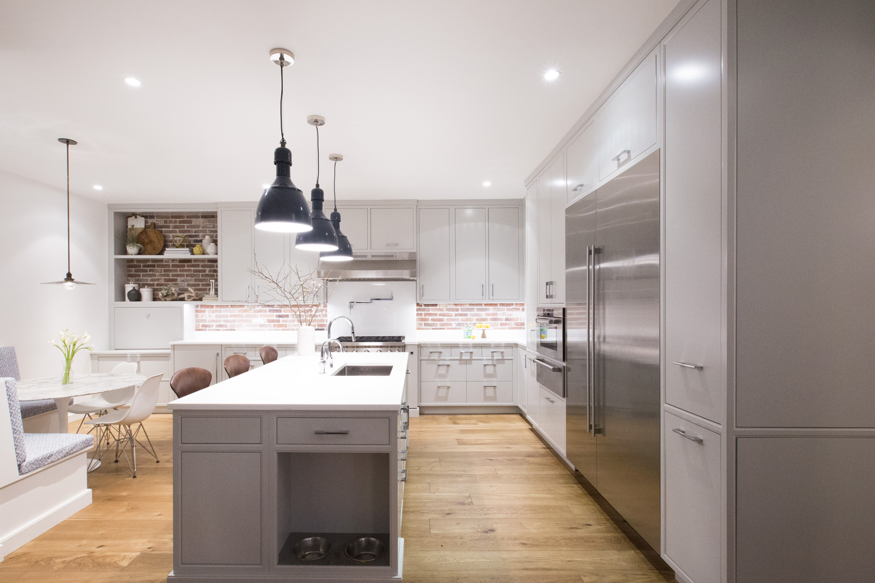 Transitional kitchen features exposed brick walls, oak flooring, center island with sink and seating, white quartz counters and fully custom flat panel grey painted cabinets by Bilotta with brushed stainless hardware. Design by Aston Smith of Bilotta Kitchens.