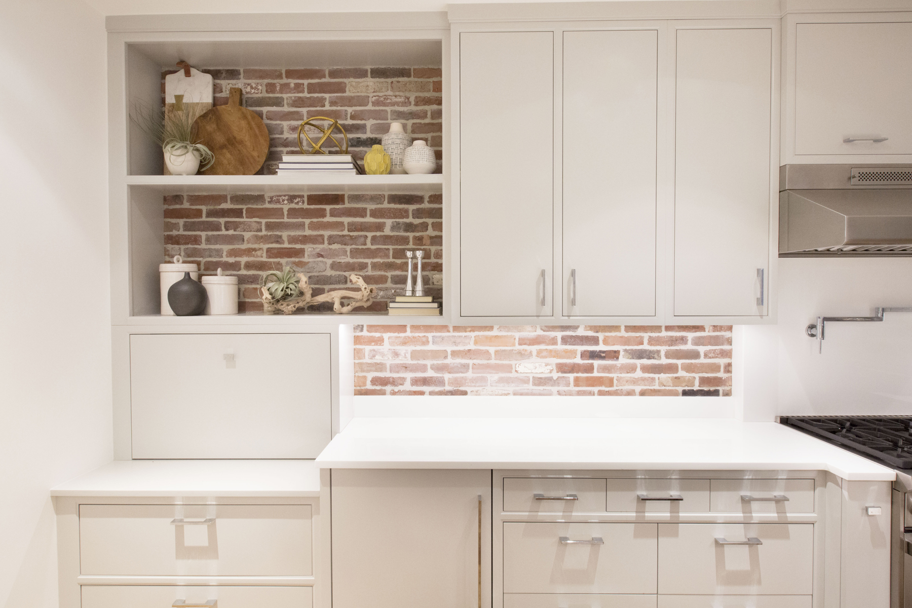 Transitional kitchen features exposed brick walls, white quartz counters, open shelving and fully custom flat panel grey painted cabinets by Bilotta and brushed stainless hardware. Design by Aston Smith of Bilotta Kitchens.