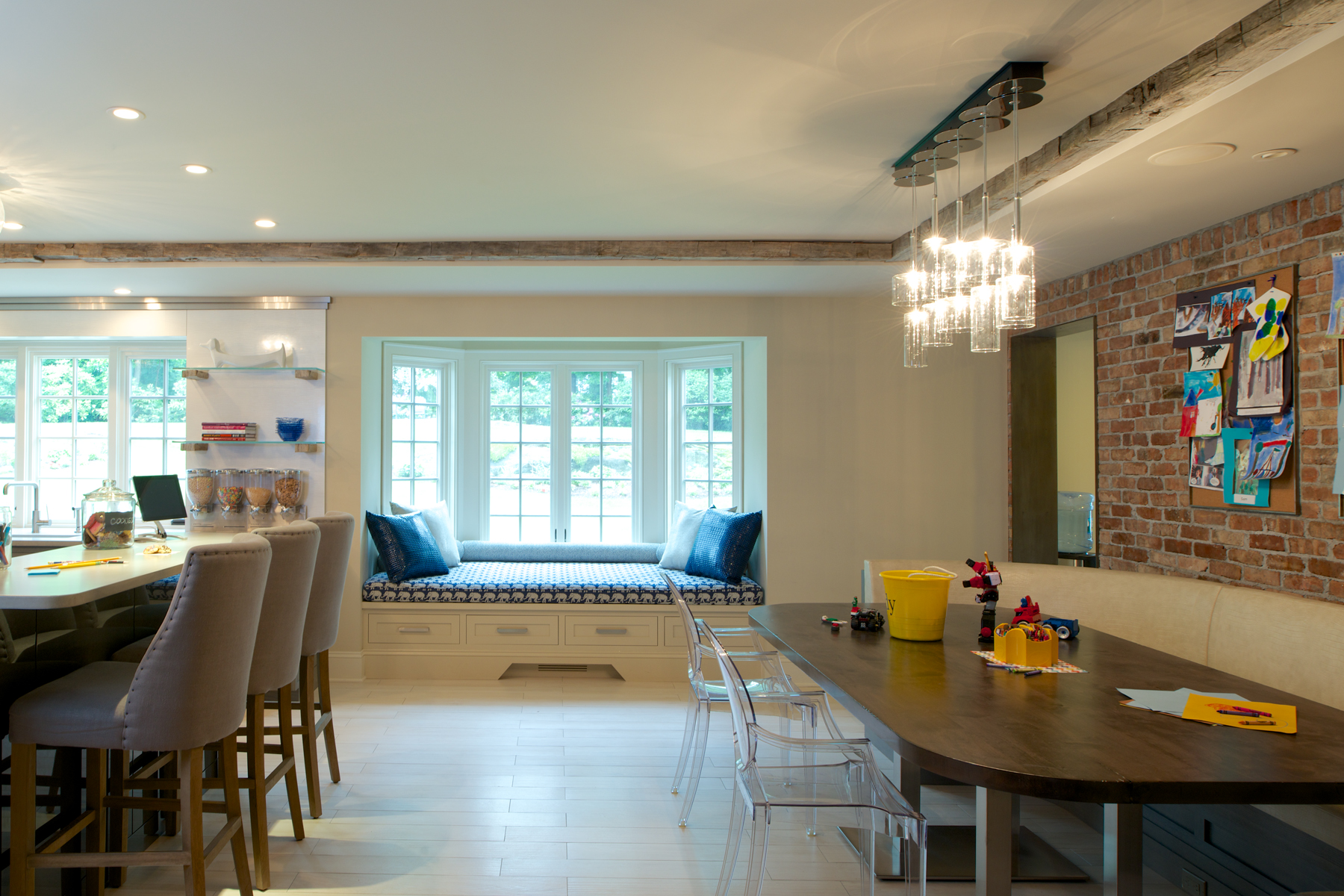 Expansive family-friendly kitchen features dining table with banquette seating and clustered pendant lighting, a built-in upholstered window seat and large island with raised seating area. Design by Jeff Eakley of Bilotta Kitchens.