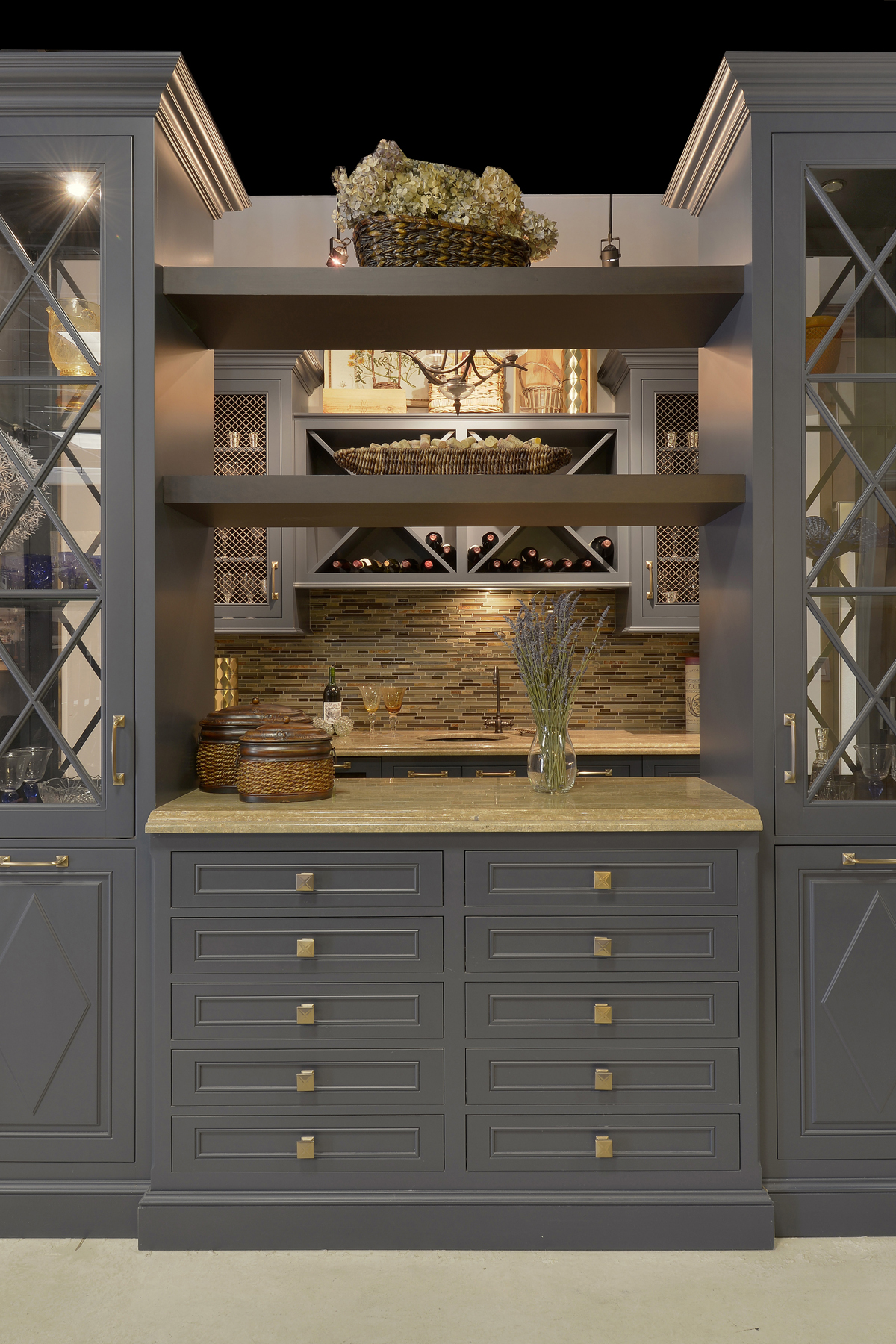 Fully custom blue painted Wood-Mode cabinets with brass hardware, featuring wine racks; glass front cabinets, and wire mesh cabinet door inserts. Designed by Paula Greer, CKD of Bilotta Kitchens.