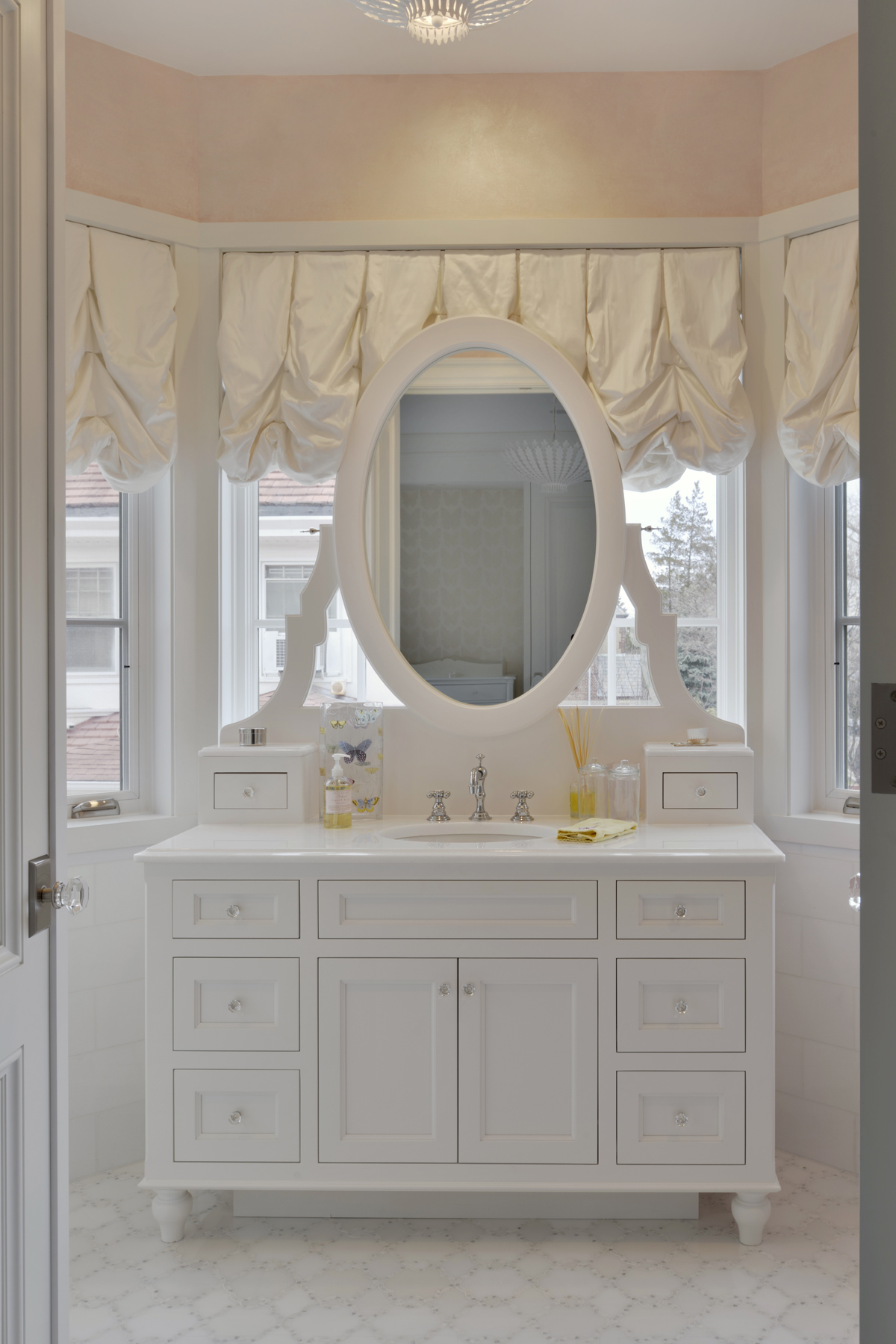 White and pale pink girl's bathroom features white balloon shades and a custom white painted built-in vanity by Bilotta Cabinetry with crystal door hardware and an oval mirror. Design by Tom Vecchio of Bilotta Kitchens.