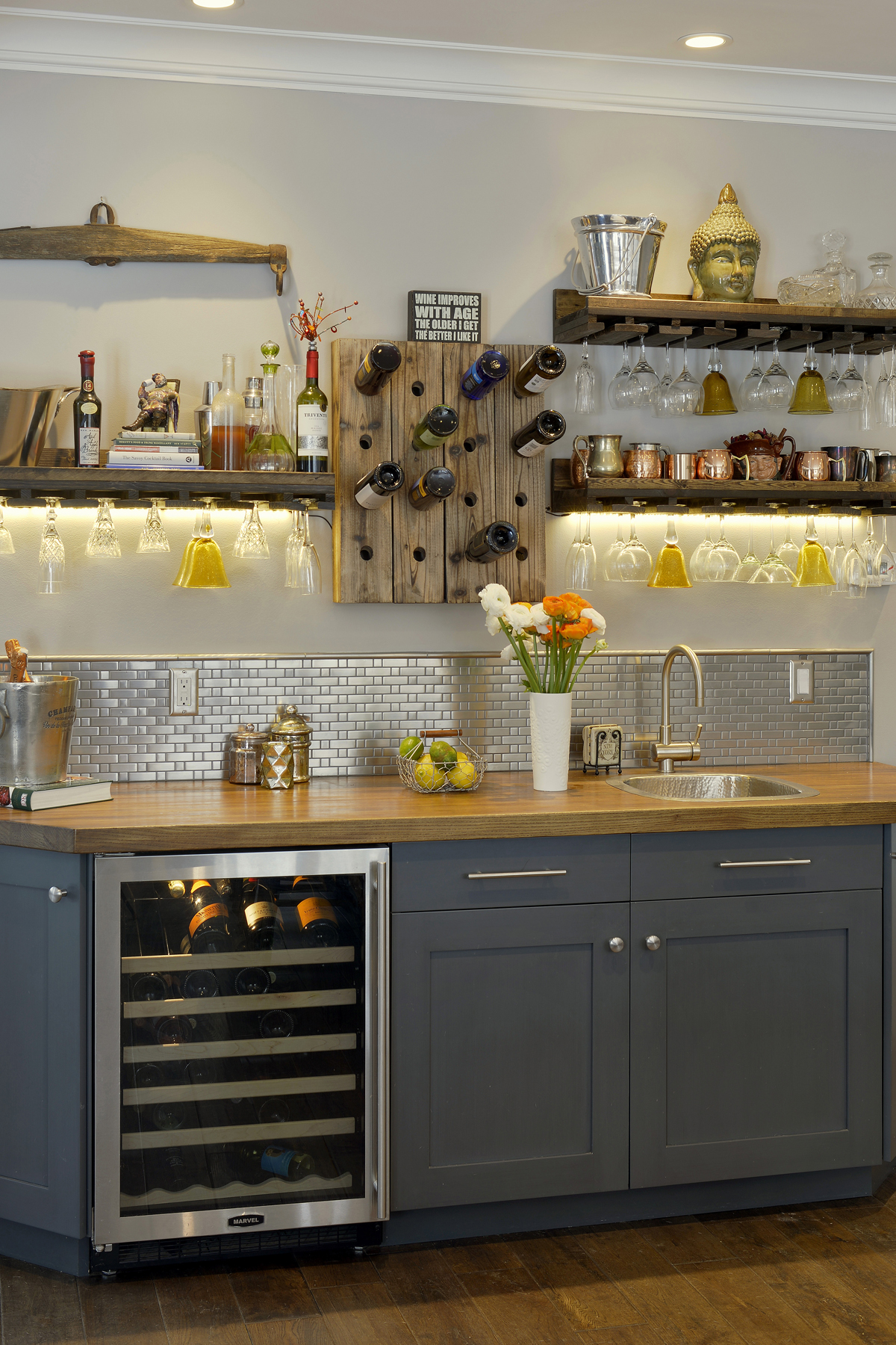Wet bar features custom grey painted shaker style frameless cabinetry with round satin stainless hardware, textured metal backsplash, butcherblock countertop and rustic floating shelves for glassware and copper vessles. Design by Paulette Gambacorta of Bilotta Kitchens.