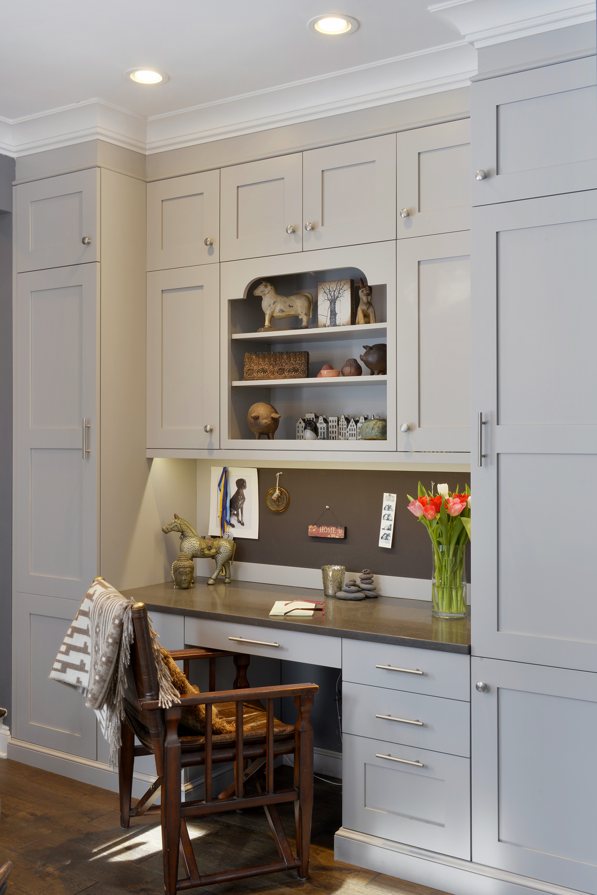 Desk area features custom light grey painted Bilotta Cabinetry with brushed stainless hardware, black quartz top and back cork board backsplash. Open shelving with custom cutout provides a small display area. Design by Paulette Gambacorta of Bilotta Kitchens.