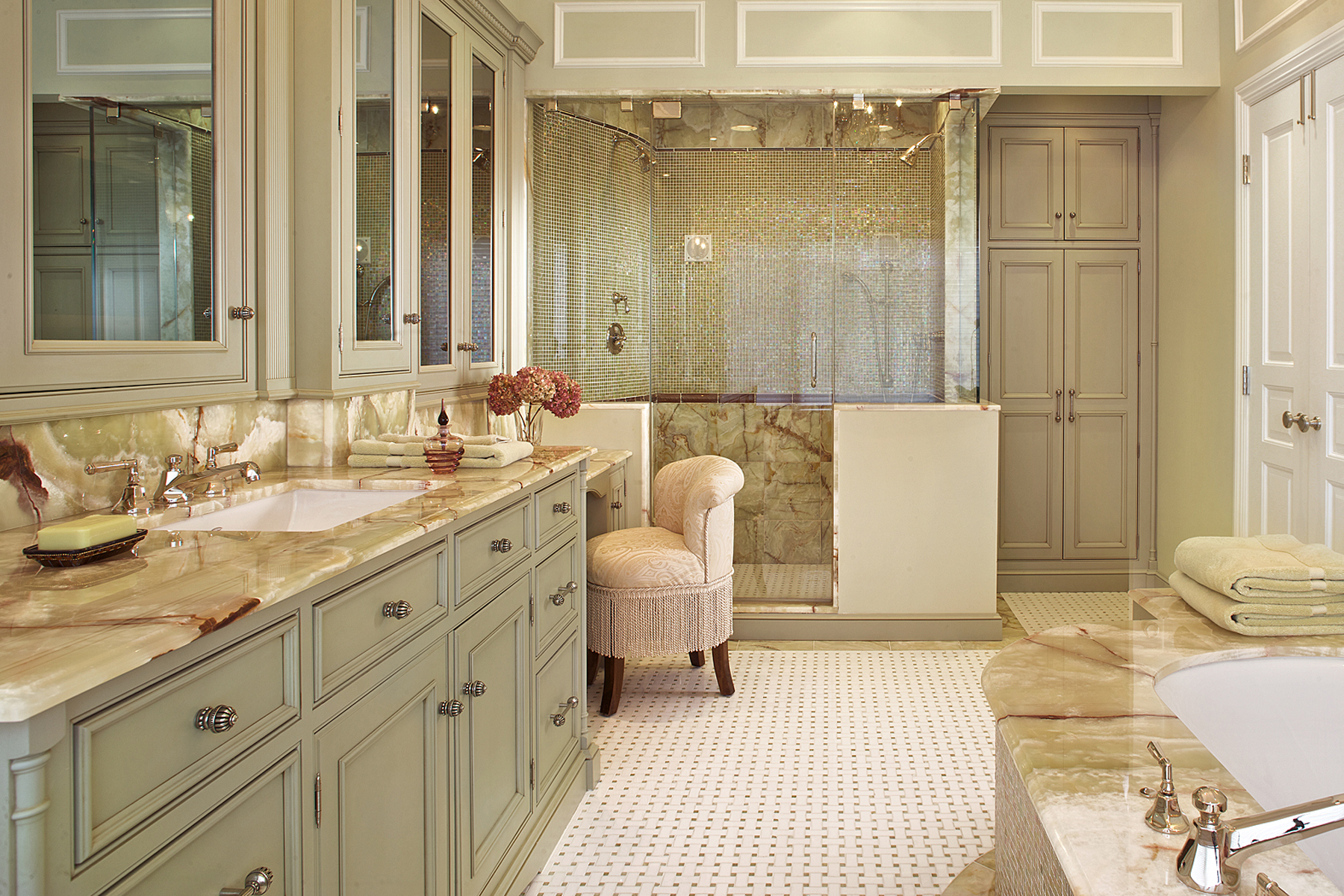 Large master bath features pistachio green painted custom vanity, medicine cabinets and linen closet by Bilotta with inset molding, mirror doors and decorative silver door hardware, light green marble countertops with brown veining, and an oversized double shower with marble up to the chair rail and small pistachio green, gold and brown tiles above the chair rail. Design by Regina Bilotta of Bilotta Kitchens.
