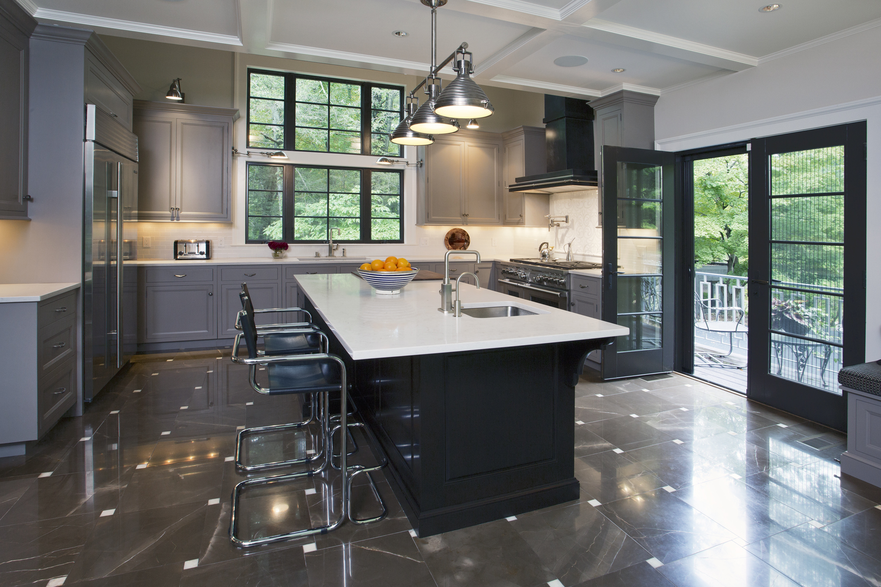 Traditional kitchen with modern accents is outfitted with fully custom cabinets from Bilotta and Wood-Mode. gray painted cabinets are paired with an island with cherry cabinet with a stain. Glass paneled patio doors open out to patio seating. Design by Paula Greer, CKD of Bilotta Kitchens.