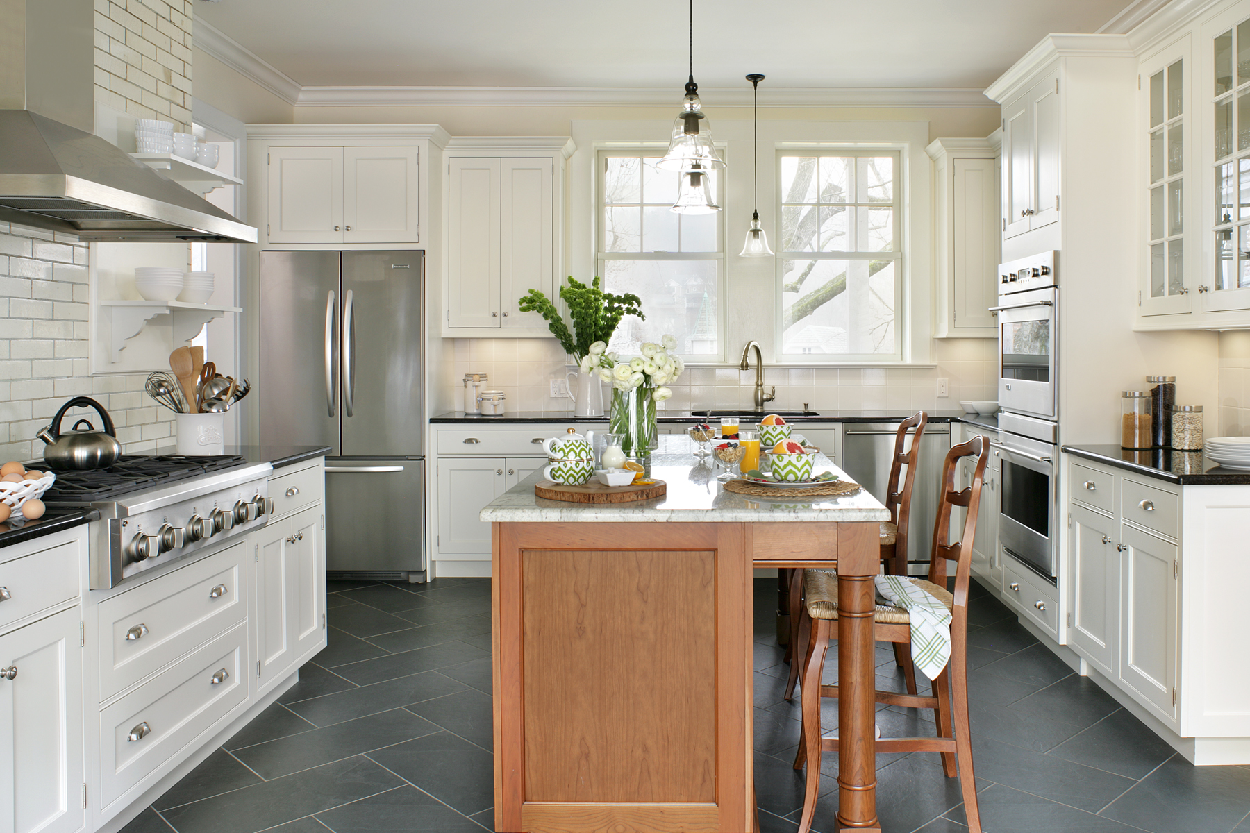 U-shaped kitchen with semi custom Brookhaven cabinets. Cherry island with seating contrasts with the white painted cabinets throughout. Designed by Danielle Florie of Bilotta Kitchens.
