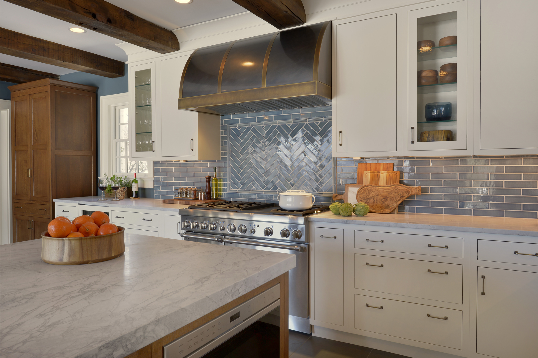 Hearth area of L-shaped expansive kitchen features blue-glazed tile backsplash in a herringbone pattern, metal hood, and fully custom white painted flat panel cabintery by Bilotta. Flat panel inset rift cut oak Bilotta Cabintry is used for the hutch and island. Design by Paulette Gambacorta of Bilotta Kitchens.