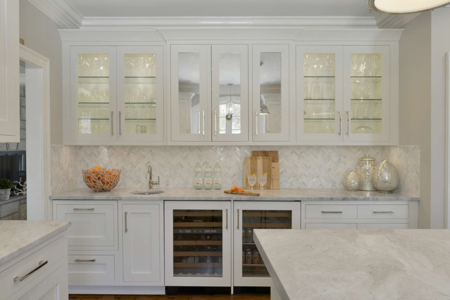 Wet bar with white and pale gray herringbone pattern backsplash and marble counter. White painted Bilotta cabinets with shaker style cabinet doors mixed with glass front cabinets with antique mirrored inserts. Designed by Linda Daniele of Bilotta Kitchens.