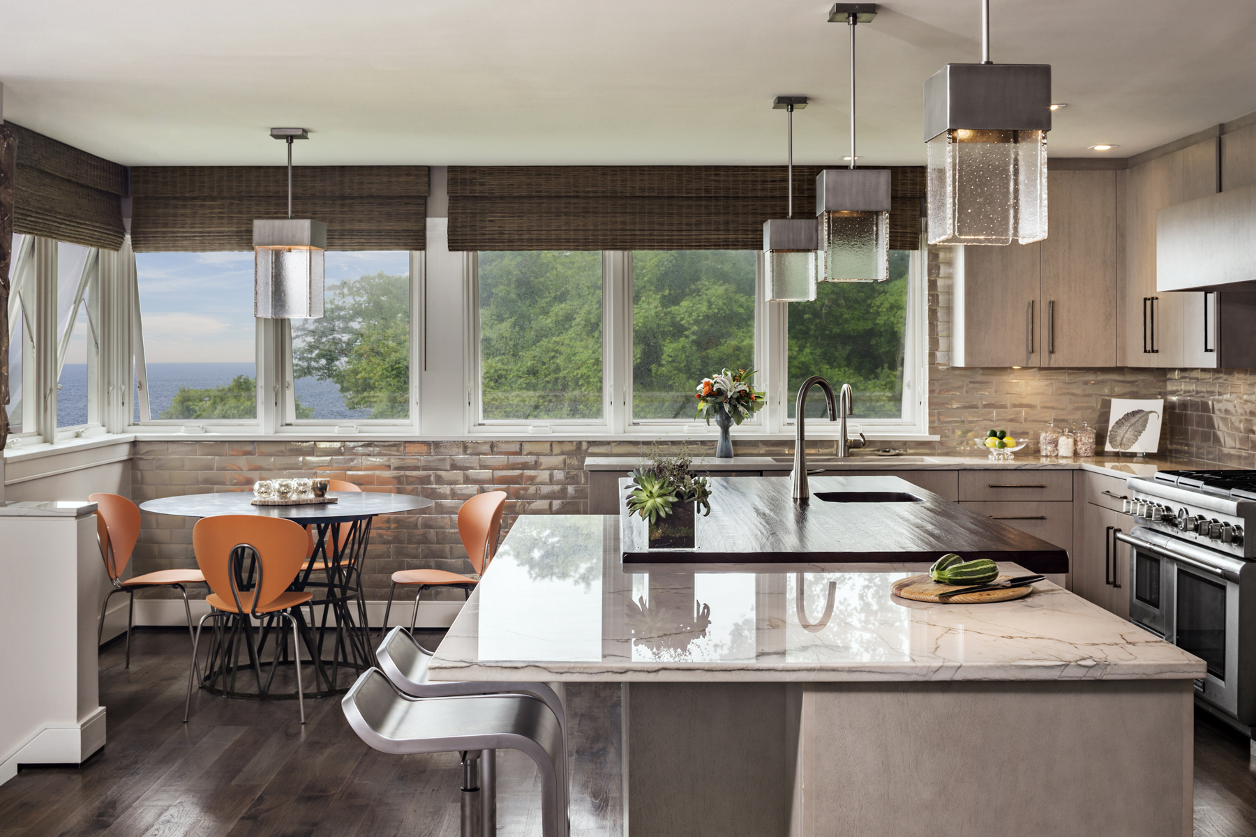 Transitional kitchen features two walls of windows, flat panel, framless, fully custom mahogany cabinets by Bilotta, metallic, tectured wallcovering, dark plank flooring and an island with marble countertop and seating. Design by Randy O'Kane, CKD, of Bilotta Kitchens.