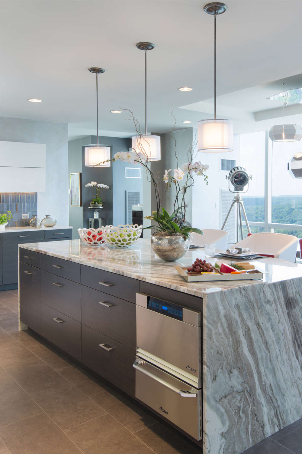 Penthouse kitchen features a large island with pendant lighting, waterfall countertop, and flat panel, frameless Artcfraft cabinet in rift cut white oak with a dark stain. Design by Jeff Eakley of Bilotta Kitchens.