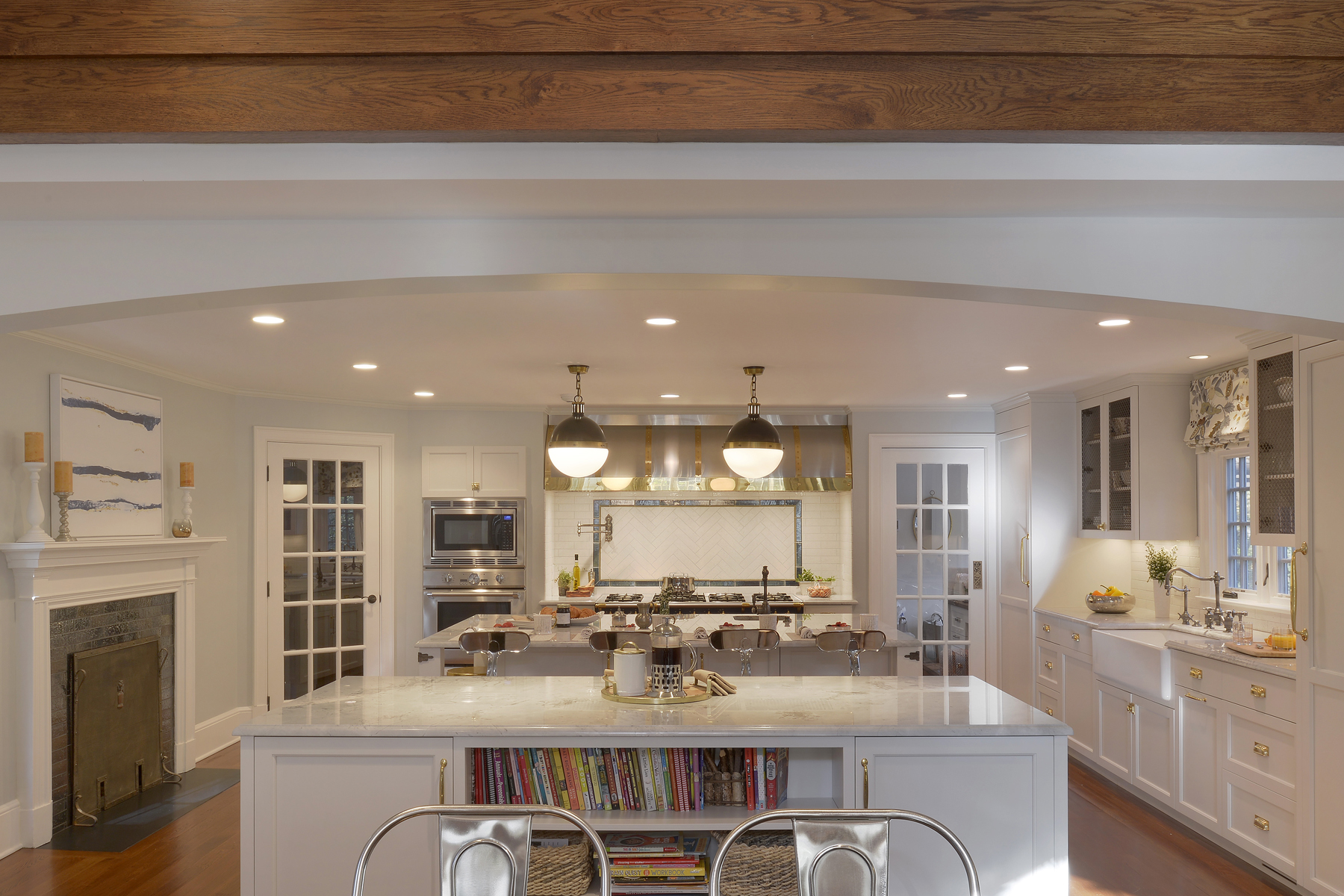 L-shaped traditional kitchen features white painted fully custom Bilotta cabinets, marble counters, double islands, fireplace, and large range area with decorative backsplash as a focal point. Designed by Randy O'Kane, CKD of Bilotta Kitchens.