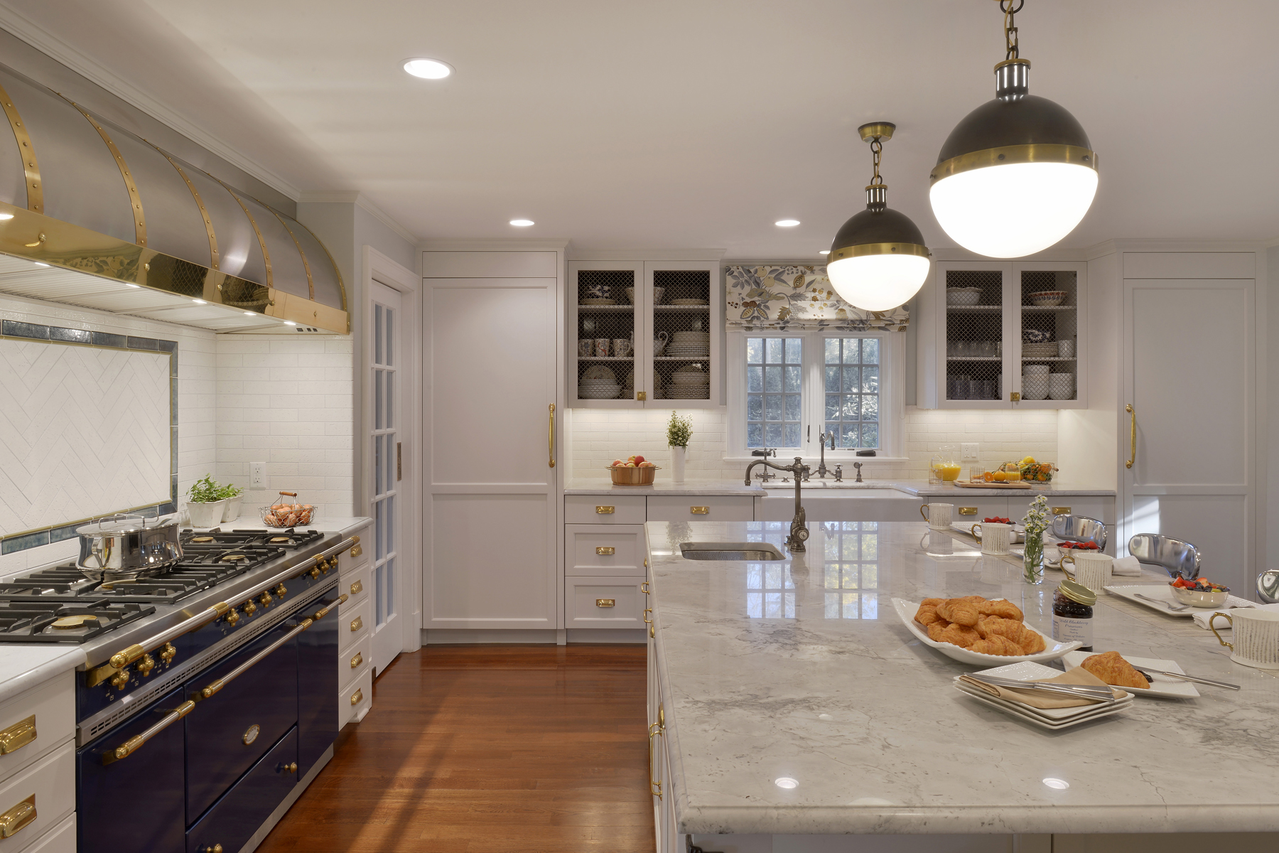 L-shaped traditional kitchen features large island with seating, natural oak flooring, marble counters, and fully custom white painted Bilotta cabinets with brass hardware. Wall cabinets have wire mesh inserts for display. Designed by Randy O'Kane, CKD of Bilotta Kitchens.