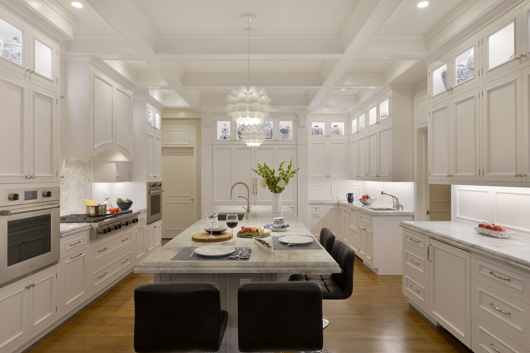 Expansive kitchen features coffered ceiling, natural oak flooring, double-tiered, white painted cabinets by Bilotta, large hearth, and a large island with seating. Top cabinets are lit and have glass fronts for display. Designed by Fabrice Garson of Bilotta Kitchens.