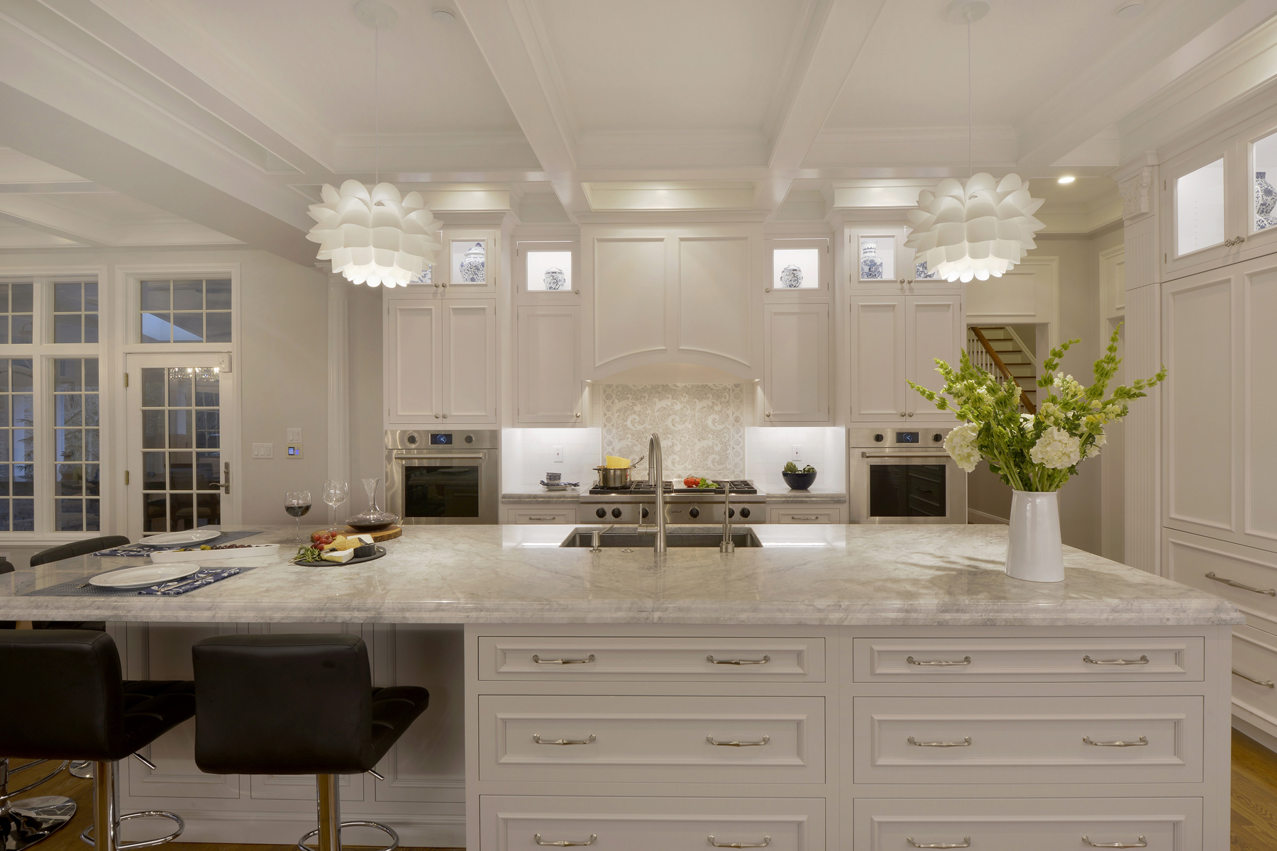 Large island with seating features marble top and fully custom white painted Bilotta cabinets. Double-tiered white painted Bilotta cabinets throughout kitchen. Designed by Fabrice Garson of Bilotta Kitchens.