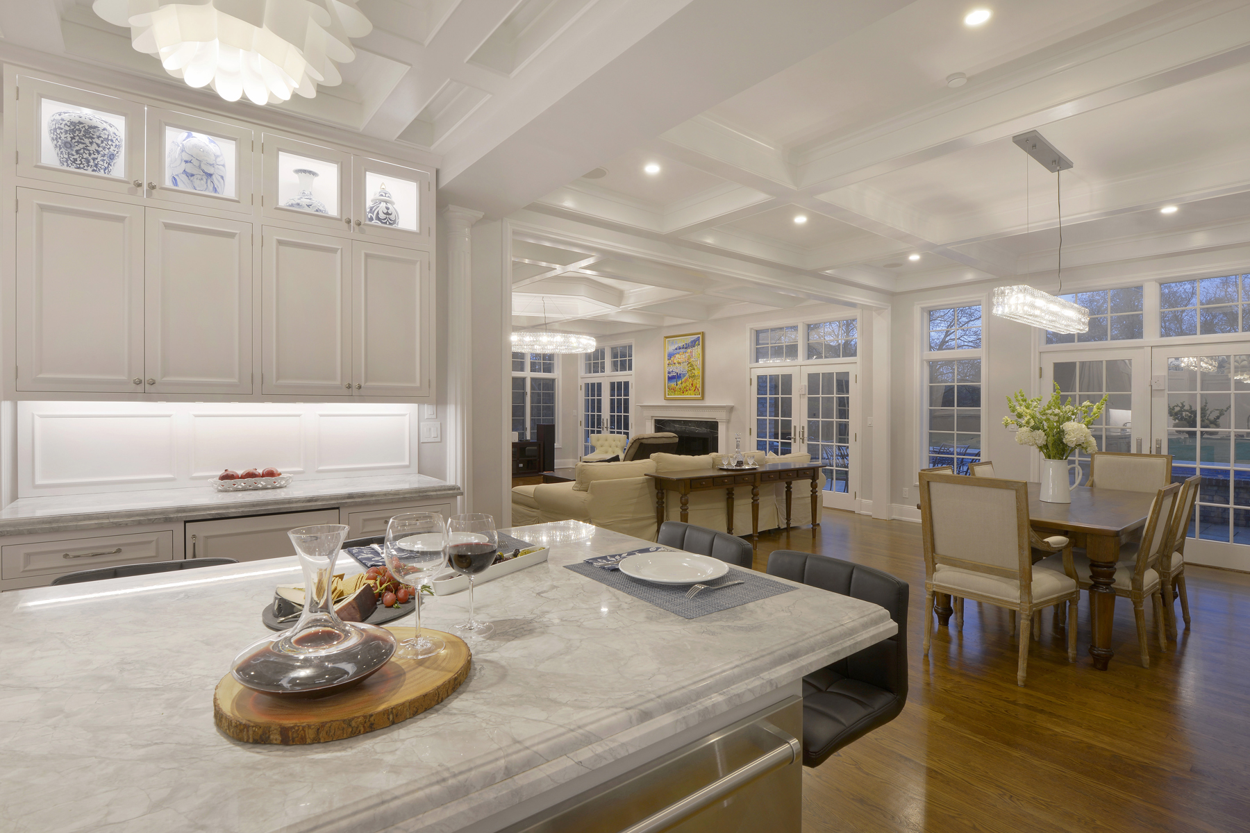Expansive kitchen with white painted fully custom Bilotta cabinets and oak flooring opens up into dining and living room areas. Large island with marble top and seating. Designed by Fabrice Garson of Bilotta Kitchens.