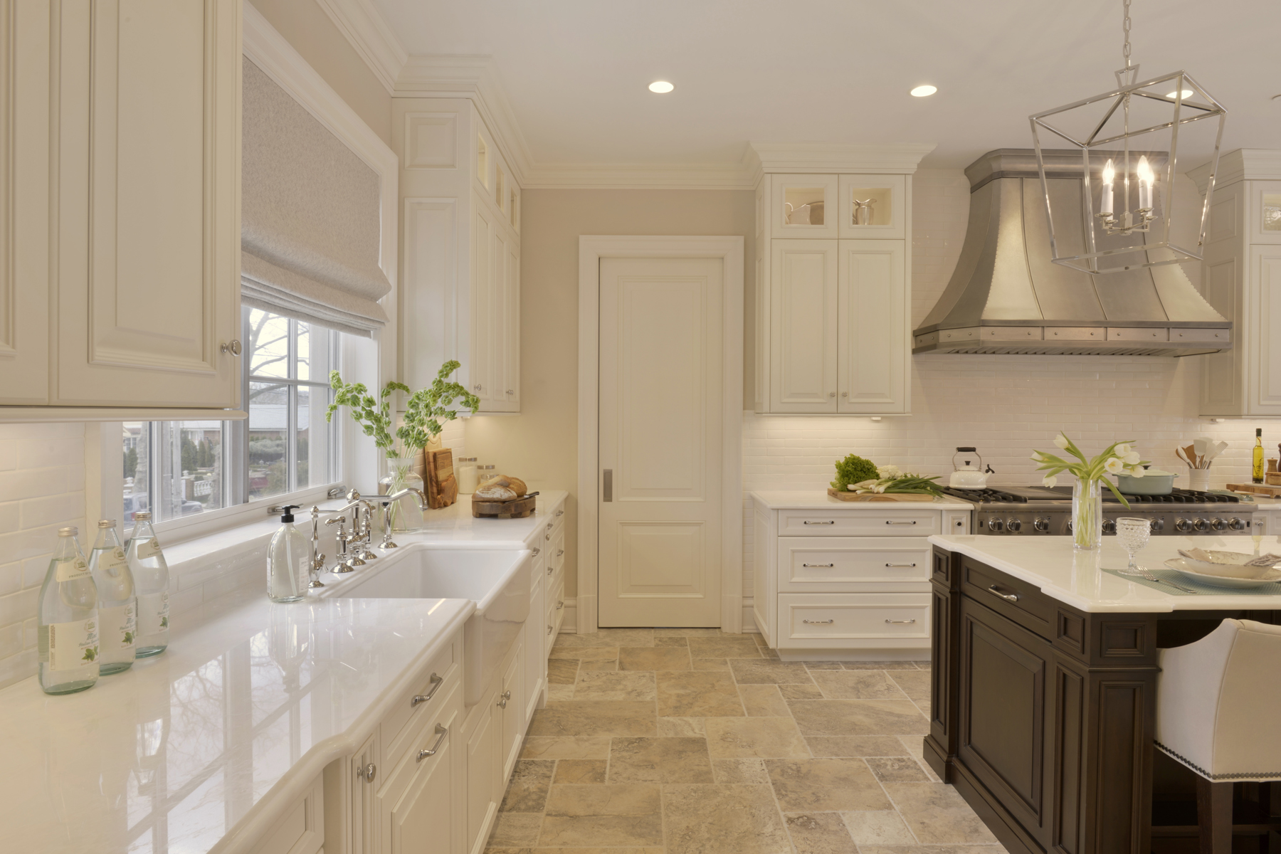 Traditional kitchen with white painted Rutt Handcrafted cabinets, white countertops, farmer's sink, white subway tiles and light flooring. Pocket door opens into butler's pantry. Designed by Tom Vecchio of Bilotta Kitchens.