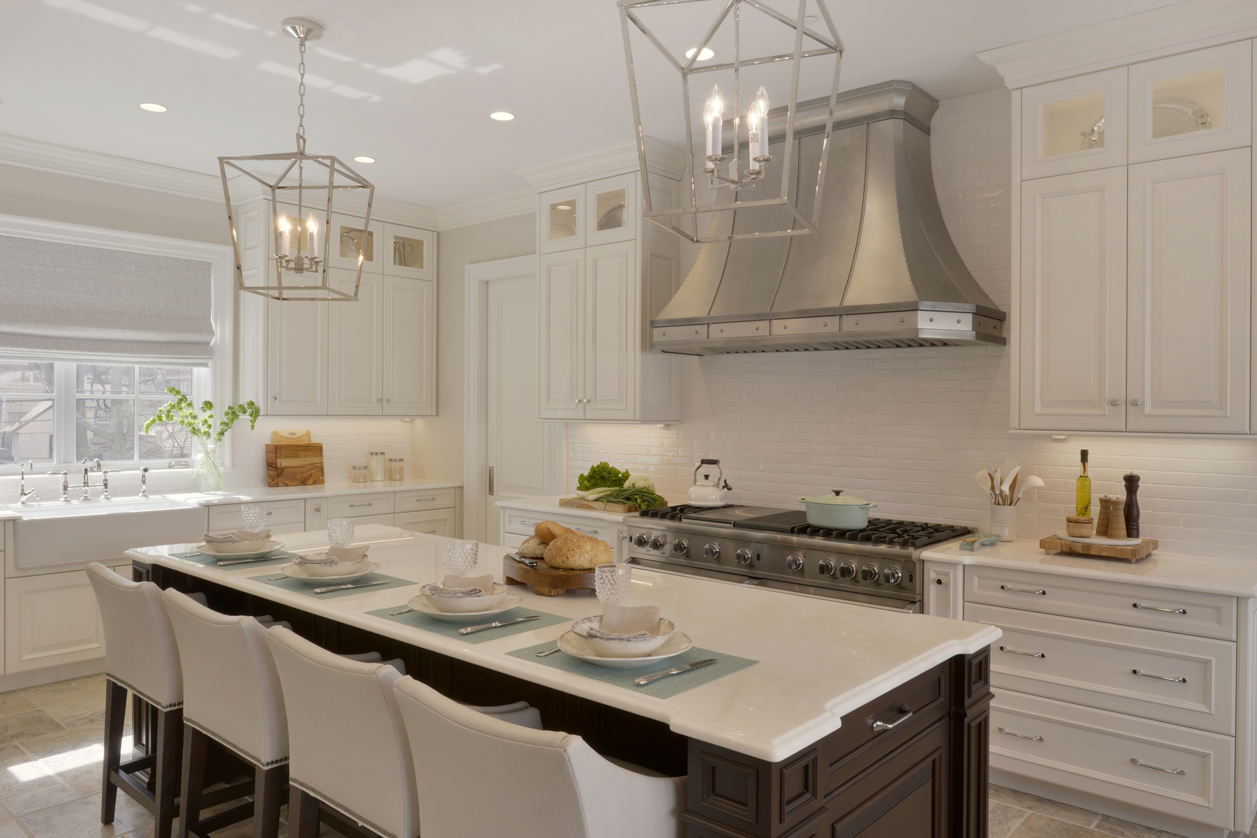 Large island with seating in expansive traditional kitchen. Island features cherry fully custom cabinets from Rutt Handcrafted cabinets. White painted Rutt cabinets and wood paneled appliances throughout the rest of the kitchen. Designed by Tom Vecchio of Bilotta Kitchens.