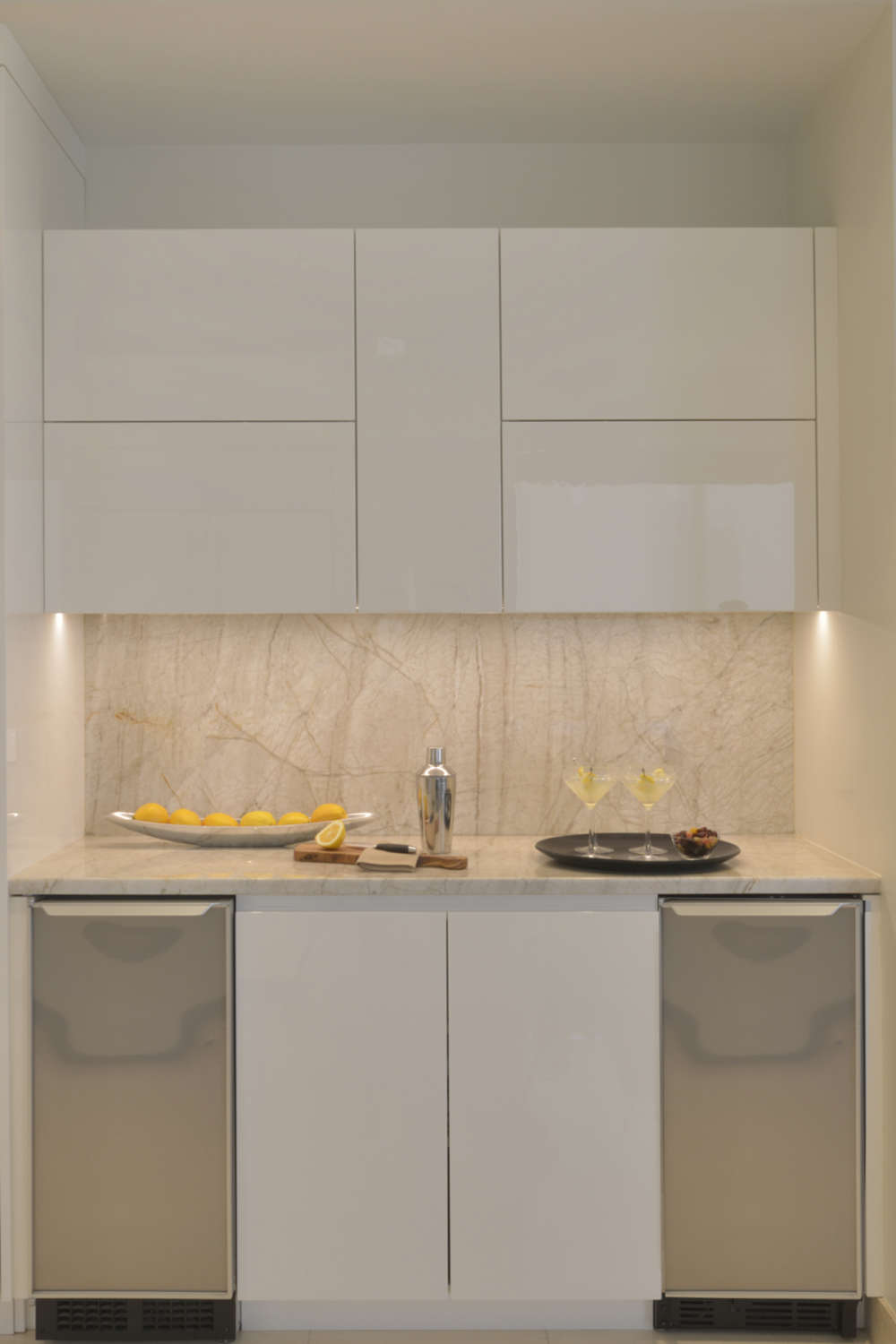Bar area of contemporary kitchen features high gloss white, flat panel fully custom Artcraft cabinetry and light marble with veining. Design by Tabitha Tepe of Bilotta Kitchens.