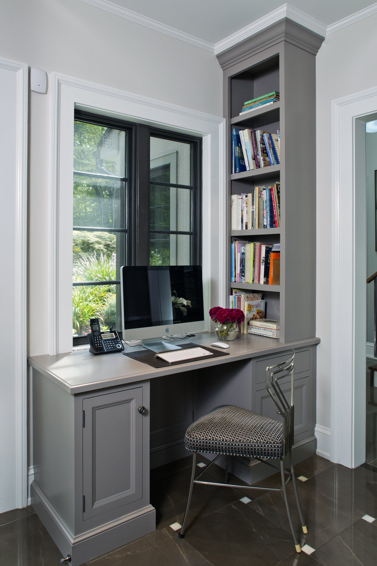 Home office features custom light grey painted Bilotta Cabinetry desk and custom built-in shelving. Desk is situated under a white-framed window with black mullions. Design by Paula Greer, CKD, of Bilotta Kitchens.