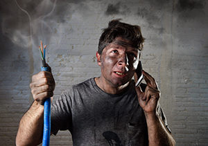 Man on cellphone covered in soot holding smoking electrical wires
