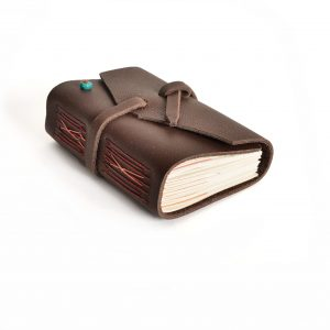 dark brown leather handmade journal laying on its side, acid free paper, accent turquoise stone, give homemade