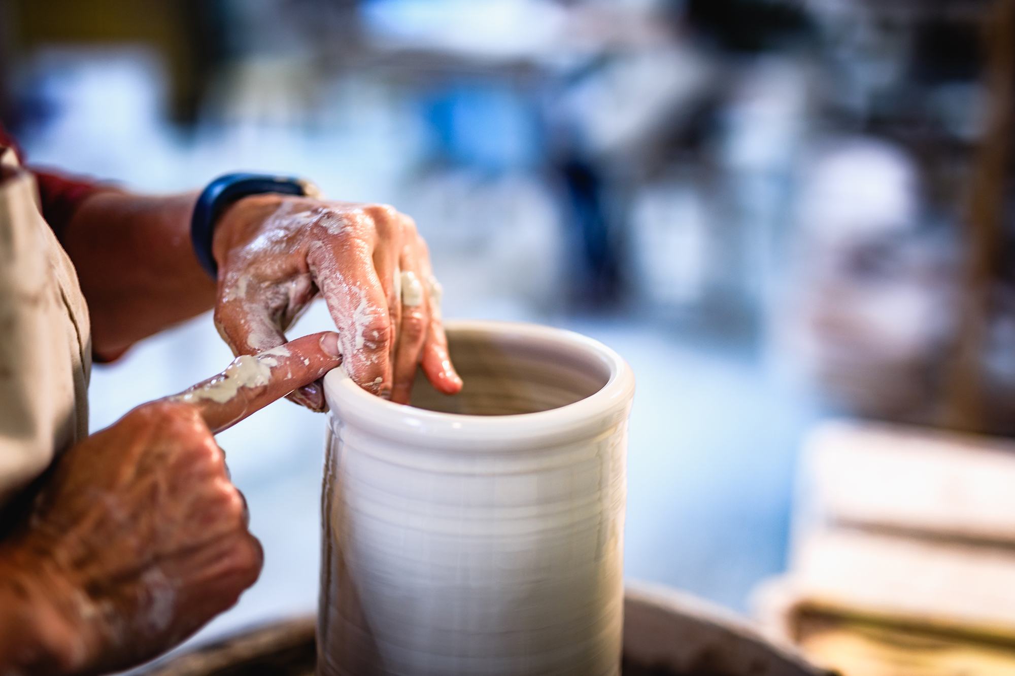 Pottery demonstration, hands throwing clay on the wheel