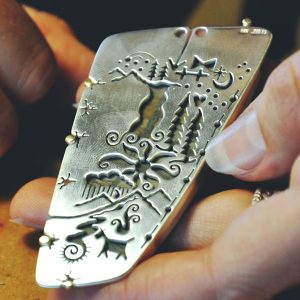 detail of silver cut out jewelry with trees, native american silver detail