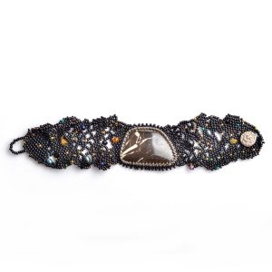 Top view of black lace woven beaded bracelet with large jasper stone and handmade silver button closure