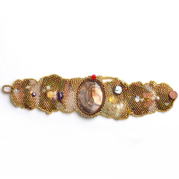 Top view of golden woven beaded bracelet with large jasper stone and copper handmade button closure