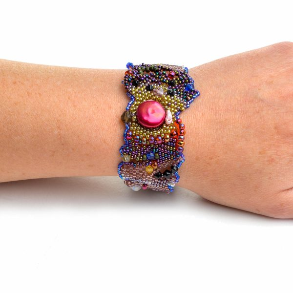 Rainbow woven beaded bracelet with red pearl on wrist