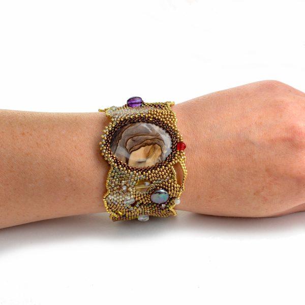 Gold asymmetrical golden jasper woven beaded bracelet on wrist of model