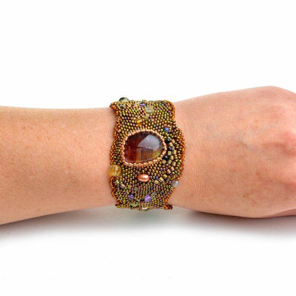 Large golden woven beaded bracelet with glass bead on models wrist